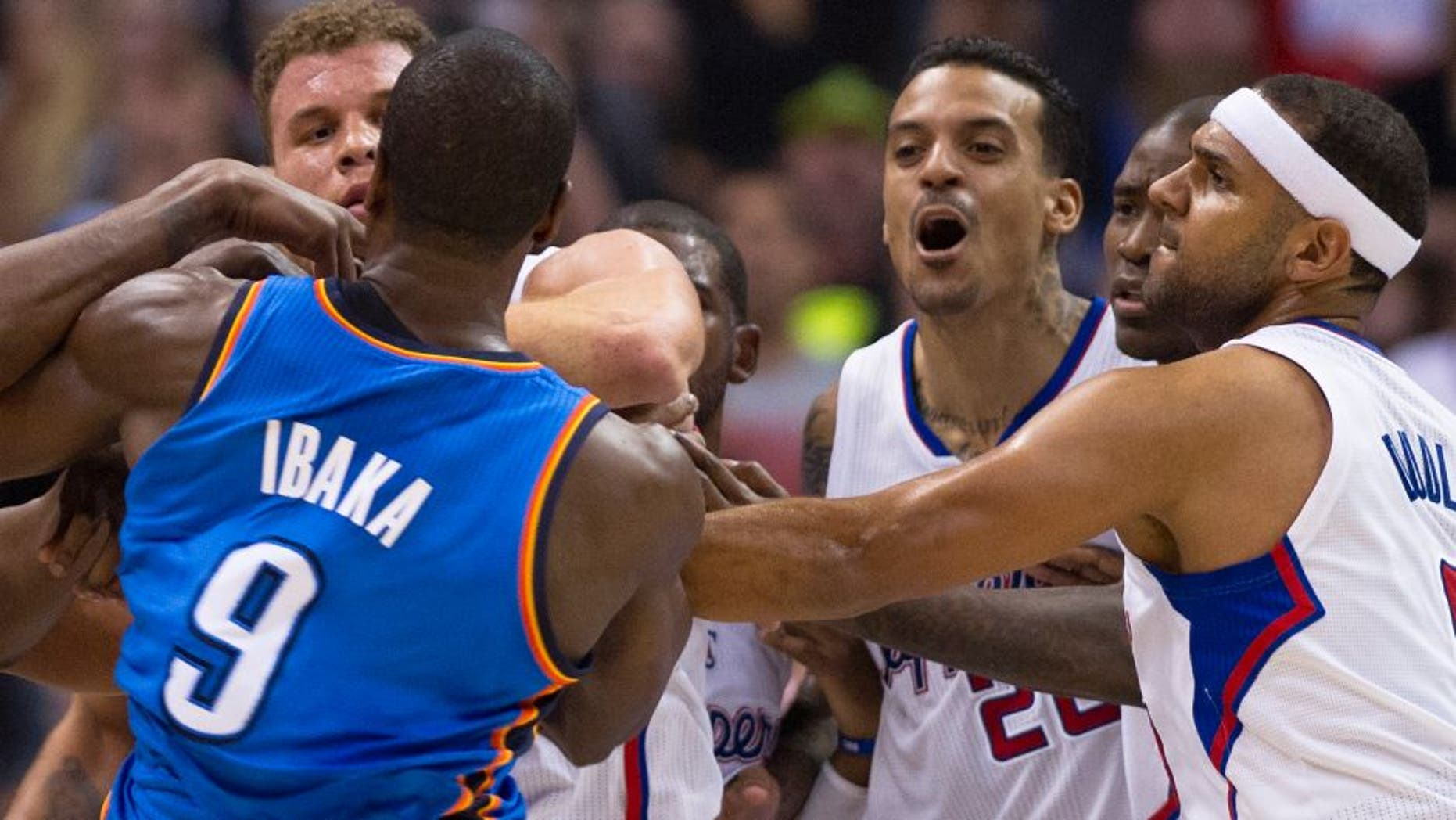 """Los Angeles Clippers Matt Barnes (2R) and Oklahoma City Thunder Serge Ibaka (L) skirmish in the final seconds of the second quarter, during NBA action, November 13, 2013 in Los Angeles, California. At far left is the Clippers Blake Griffin and at right is the Clippers Jared Dudley. The Los Angeles Times reported November 14, 2013 that in the final seconds of the second quarter of Wednesday's game between the Clippers and the Oklahoma City Thunder, Blake Griffin and Serge Ibaka got their arms entangled while trying to grab a rebound. They wrestled for a few seconds, then Matt Barnes intervened and shoved Ibaka, who responded by trying to push Barnes while apparently preparing to throw a punch. After Barnes left the court, he sent this tweet from the locker room, which was later taken down because it included an epithet and a curse word: """"I love my teammates like family, but I'm DONE standing up for these ...! All this ... does is cost me money."""" Doc Rivers said he was disappointed by Barnes' words after the Clippers secured a 111-103 victory at Staples Center. AFP PHOTO / Robyn Beck (Photo credit should read ROBYN BECK/AFP/Getty Images)"""