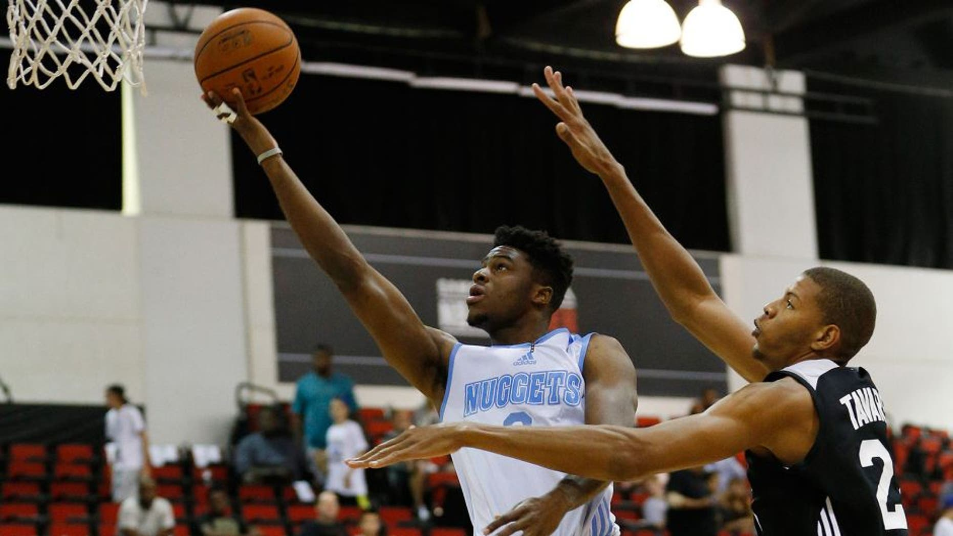 Denver Nuggets' Emmanuel Mudiay, left, goes up for a shot against the Atlanta Hawks' Walter Tavares during the first half of an NBA summer league basketball game Friday, July 10, 2015, in Las Vegas. (AP Photo/John Locher)