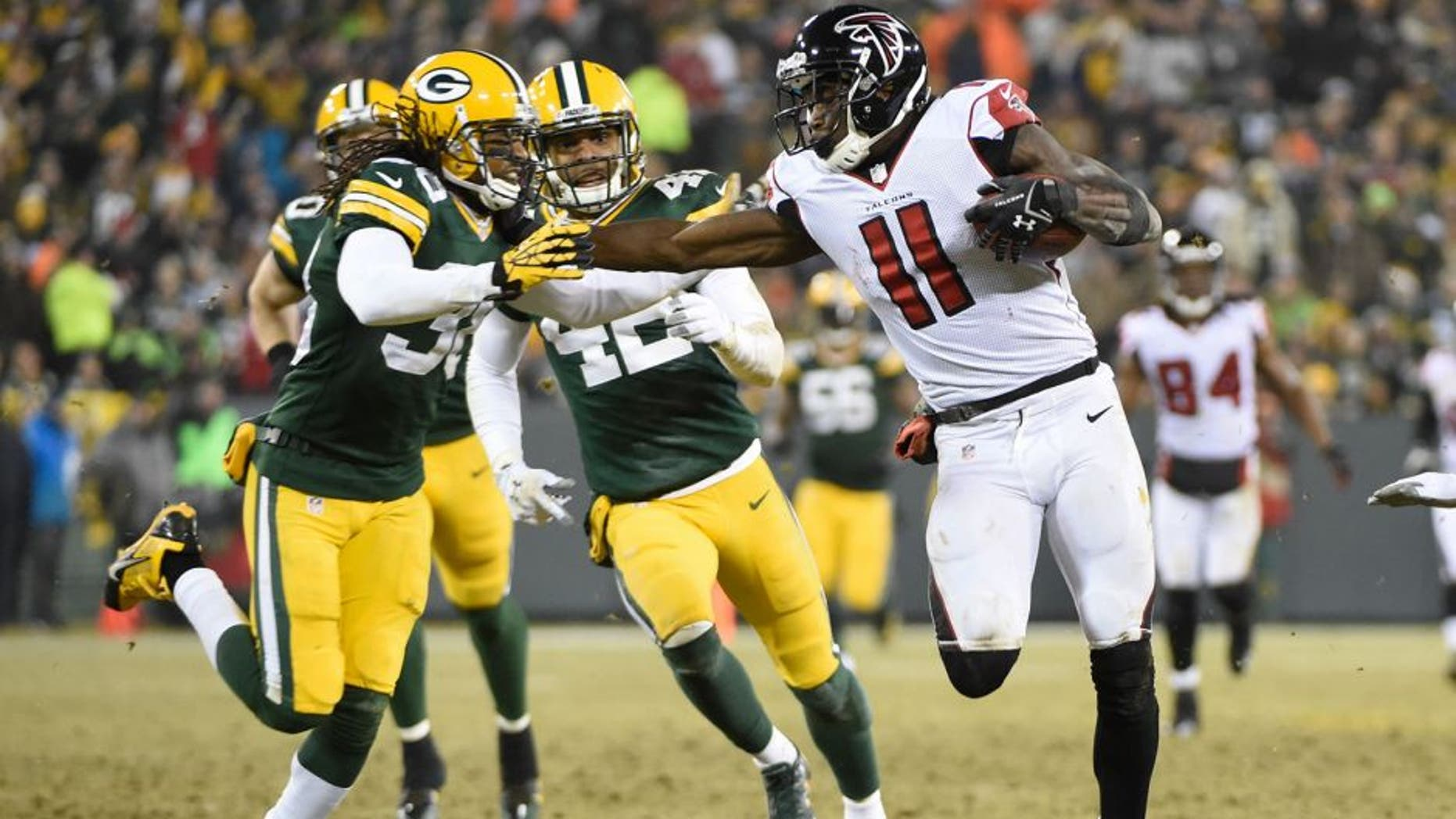 Dec 8, 2014; Green Bay, WI, USA; Atlanta Falcons wide receiver Julio Jones (11) tries to break away from Green Bay Packers cornerback Tramon Williams (38) after catching a pss in the third quarter at Lambeau Field. Mandatory Credit: Benny Sieu-USA TODAY Sports