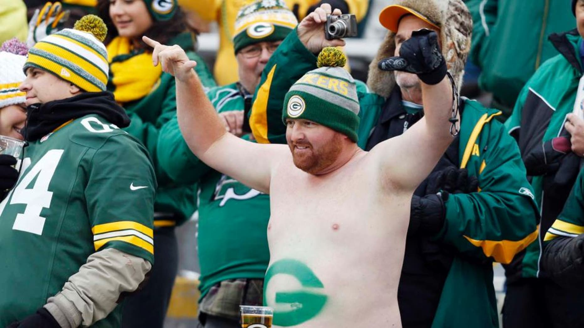 Green Bay Packers fan Cody Drinkle takes his shirt off in the stands during the first half.