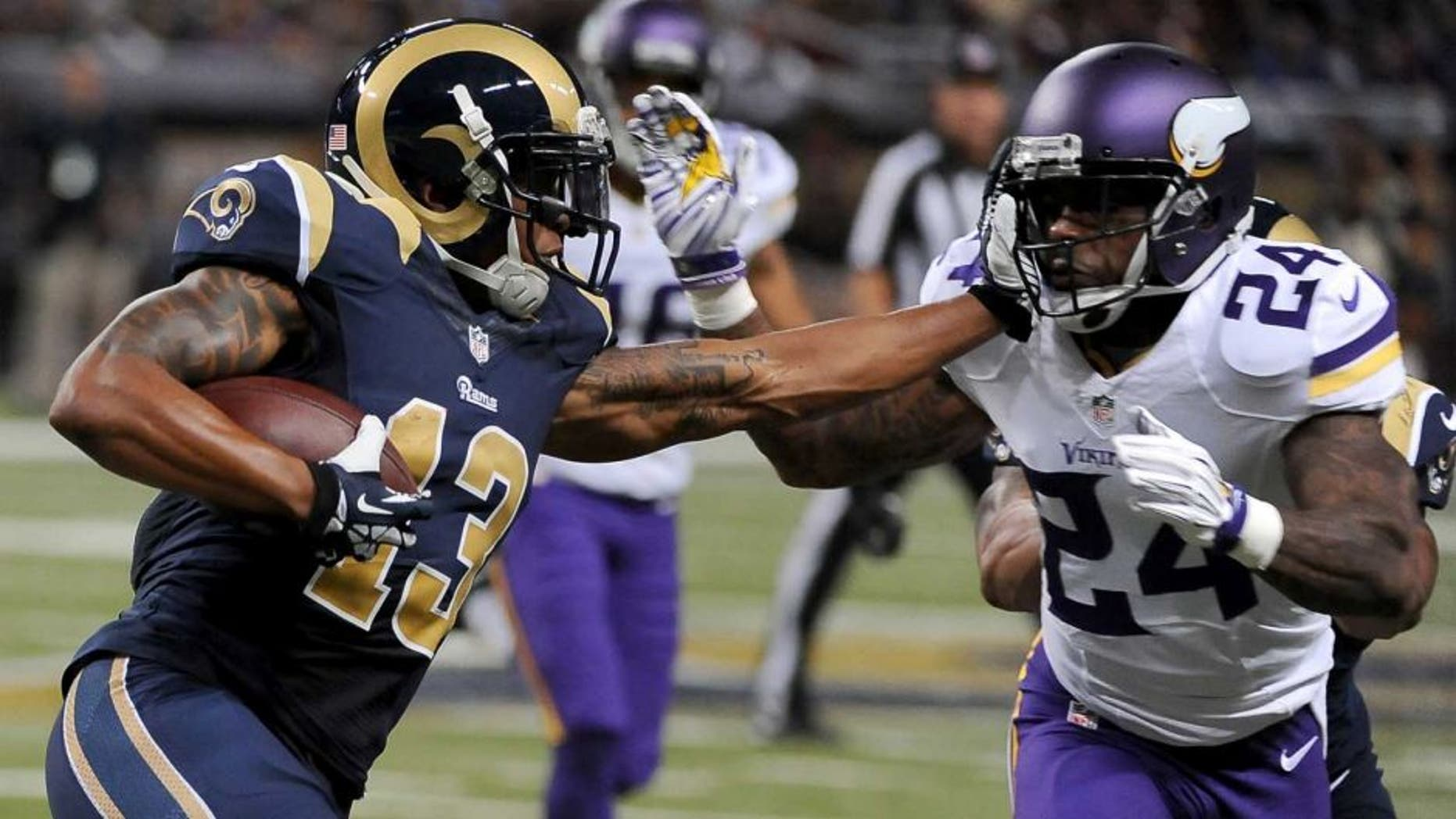St. Louis Rams wide receiver Chris Givens (left) runs with the ball for a 4-yard gain before being stopped by Minnesota Vikings cornerback Captain Munnerlyn during the second quarter in St. Louis. Munnerlyn was also given a 15-yard unnecessary roughness penalty on the play.