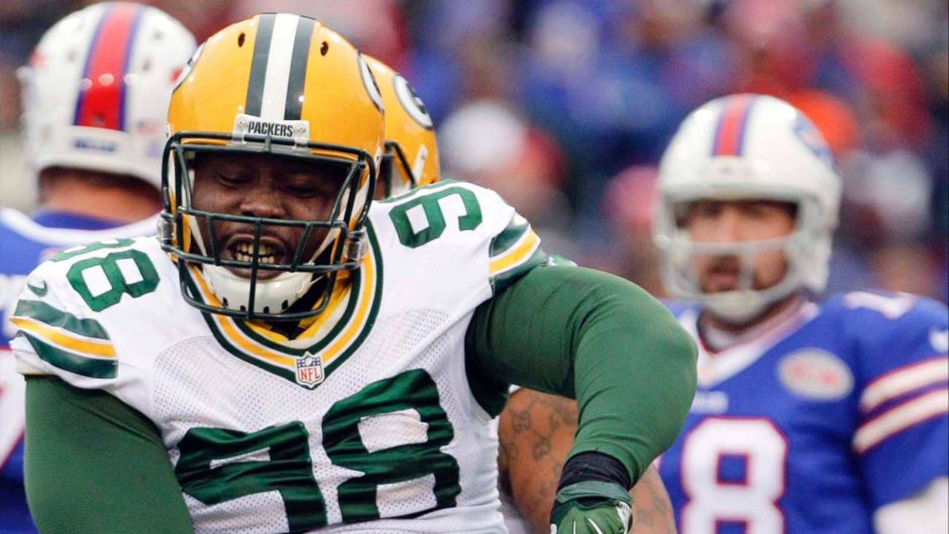 Green Bay Packers nose tackle Letroy Guion celebrates a sack of Buffalo Bills quarterback Kyle Orton (back) during the first half.