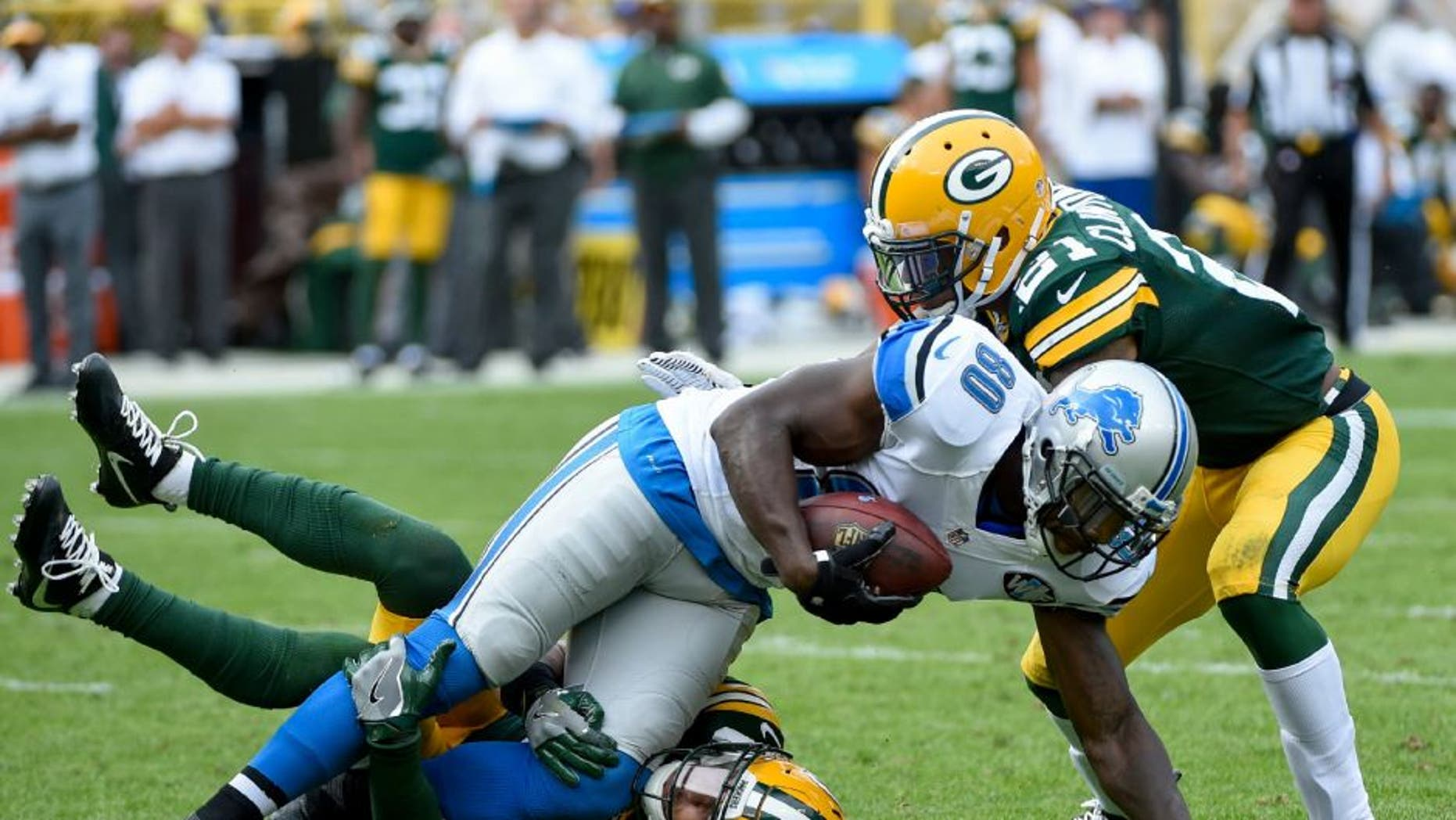 Detroit Lions wide receiver Anquan Boldin is tackled by Green Bay Packers defensive back Micah Hyde and safety Ha Ha Clinton-Dix.