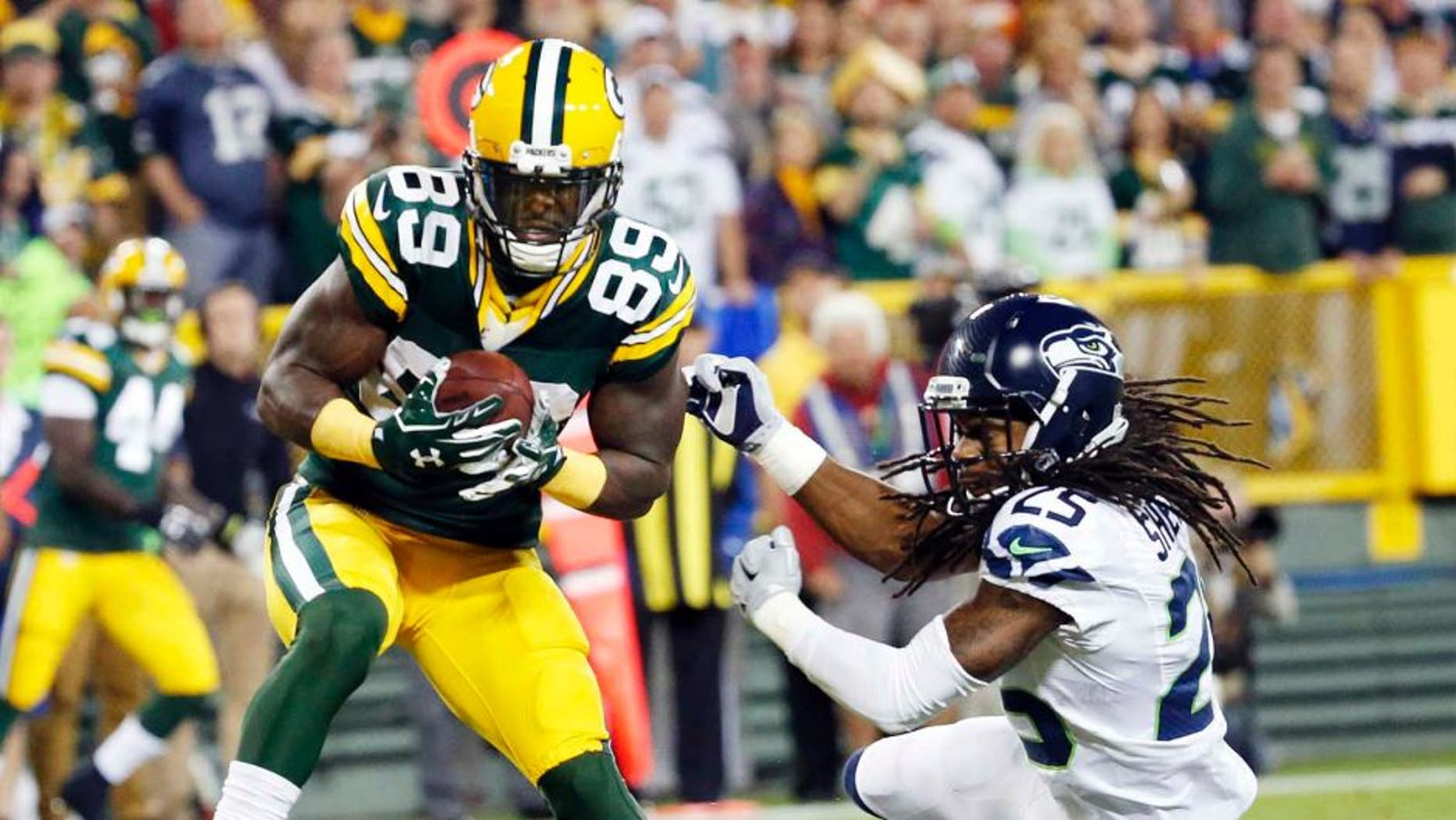 The Green Bay Packers' James Jones catches a touchdown pass in front of the Seattle Seahawks' Richard Sherman during the first half of an NFL football game Sunday, Sept. 20, 2015, in Green Bay, Wis.