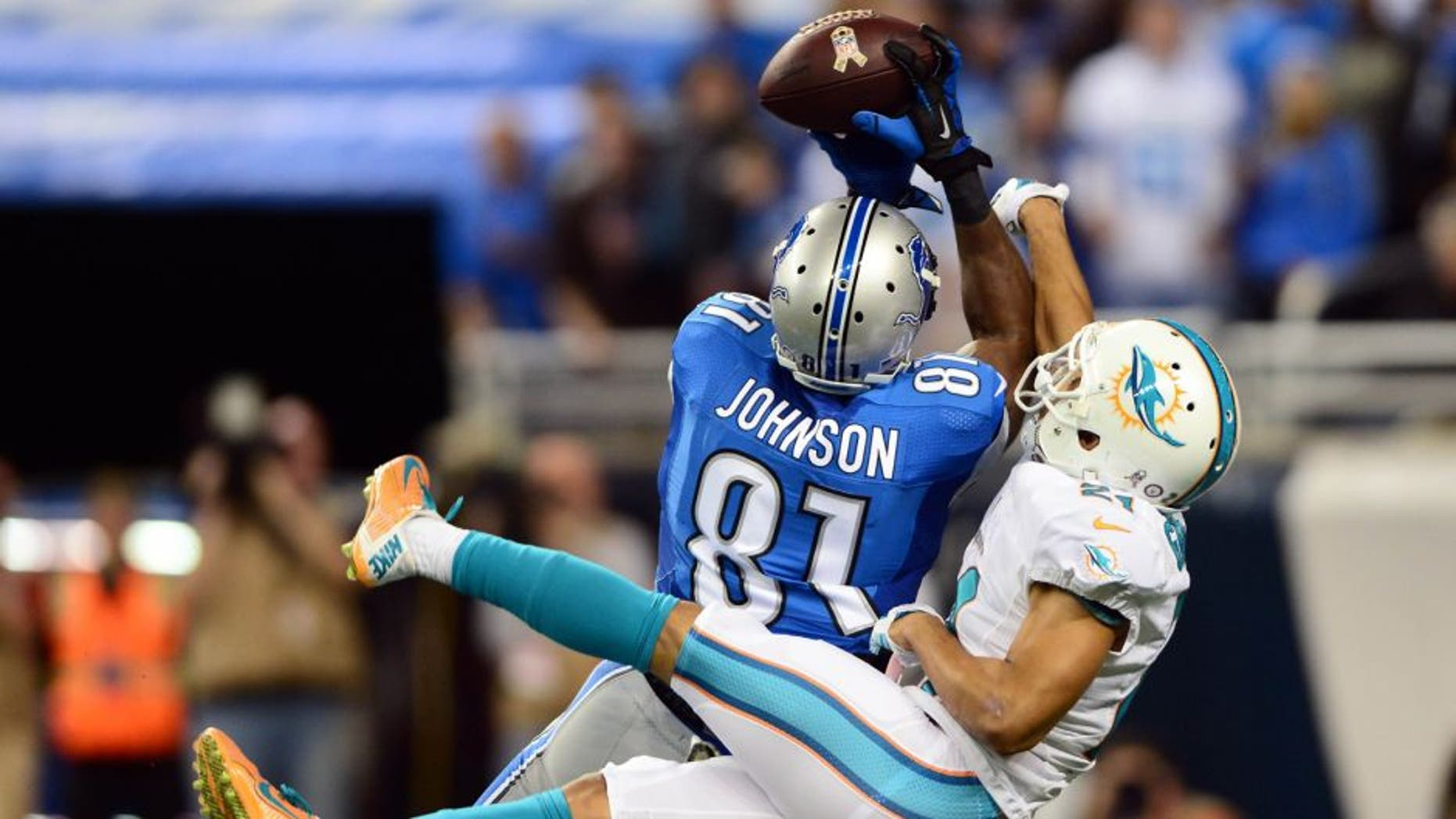 Nov 9, 2014; Detroit, MI, USA; Detroit Lions wide receiver Calvin Johnson (81) catches a pass while being defended by Miami Dolphins cornerback Brent Grimes (21) for a touchdown during the first quarter at Ford Field. Mandatory Credit: Andrew Weber-USA TODAY Sports