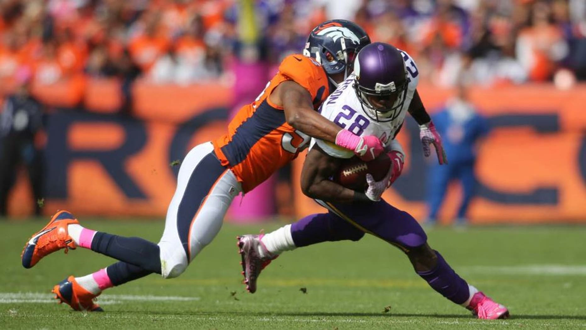 Minnesota Vikings running back Adrian Peterson is taken down by Denver Broncos inside linebacker Brandon Marshall during the first half at Sports Authority Field at Mile High in Denver on Sunday, Oct. 4, 2015.