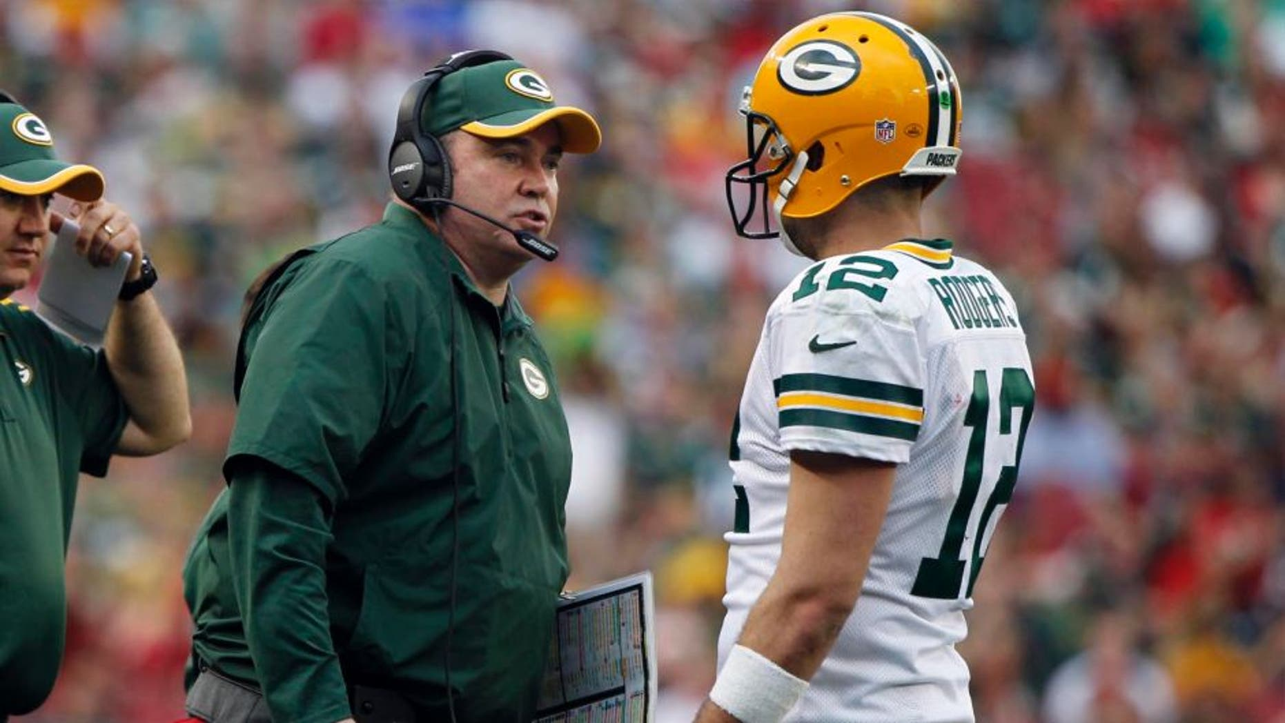 Dec 21, 2014; Tampa, FL, USA; Green Bay Packers head coach Mike McCarthy talks with quarterback Aaron Rodgers (12) against the Tampa Bay Buccaneers during the second half at Raymond James Stadium. Green Bay Packers defeated the Tampa Bay Buccaneers 20-3. Mandatory Credit: Kim Klement-USA TODAY Sports