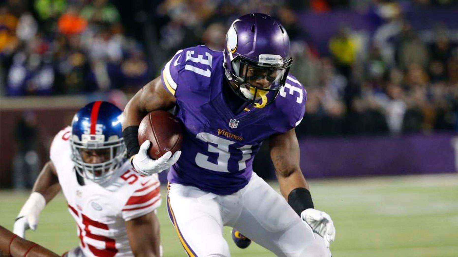 Minnesota Vikings running back Jerick McKinnon jumps over New York Giants defenders during the first half Sunday, Dec. 27, 2015, in Minneapolis.