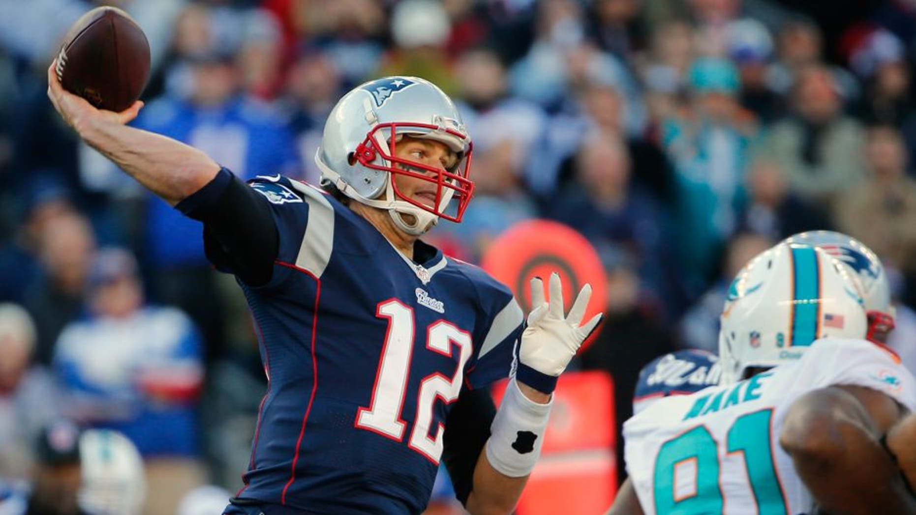 Dec 14, 2014; Foxborough, MA, USA; New England Patriots quarterback Tom Brady (12) throws the ball against the Miami Dolphins during the first half at Gillette Stadium. Mandatory Credit: Winslow Townson-USA TODAY Sports