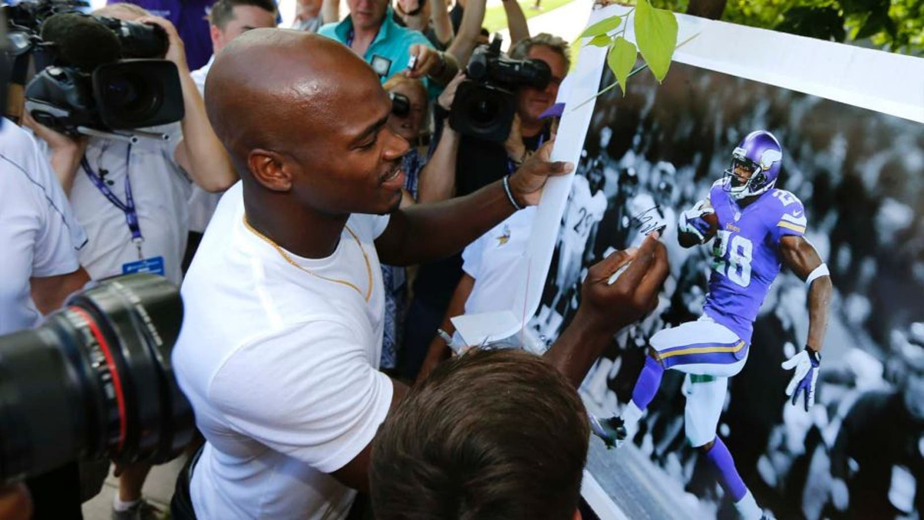 Minnesota Vikings running back Adrian Peterson signs autograph as he reports to an NFL football training camp at Minnesota State University Saturday, July 25, 2015, in Mankato, Minn.