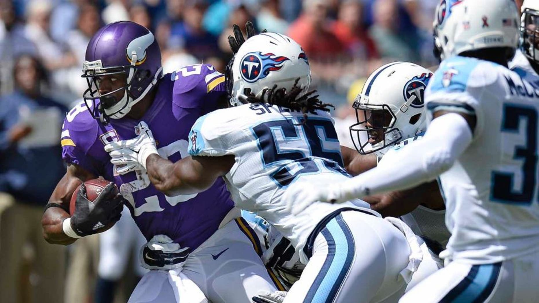 Minnesota Vikings running back Adrian Peterson tries to get past Tennessee Titans defenders including Sean Spence in the first half Sunday, Sept. 11, 2016, in Nashville, Tenn.