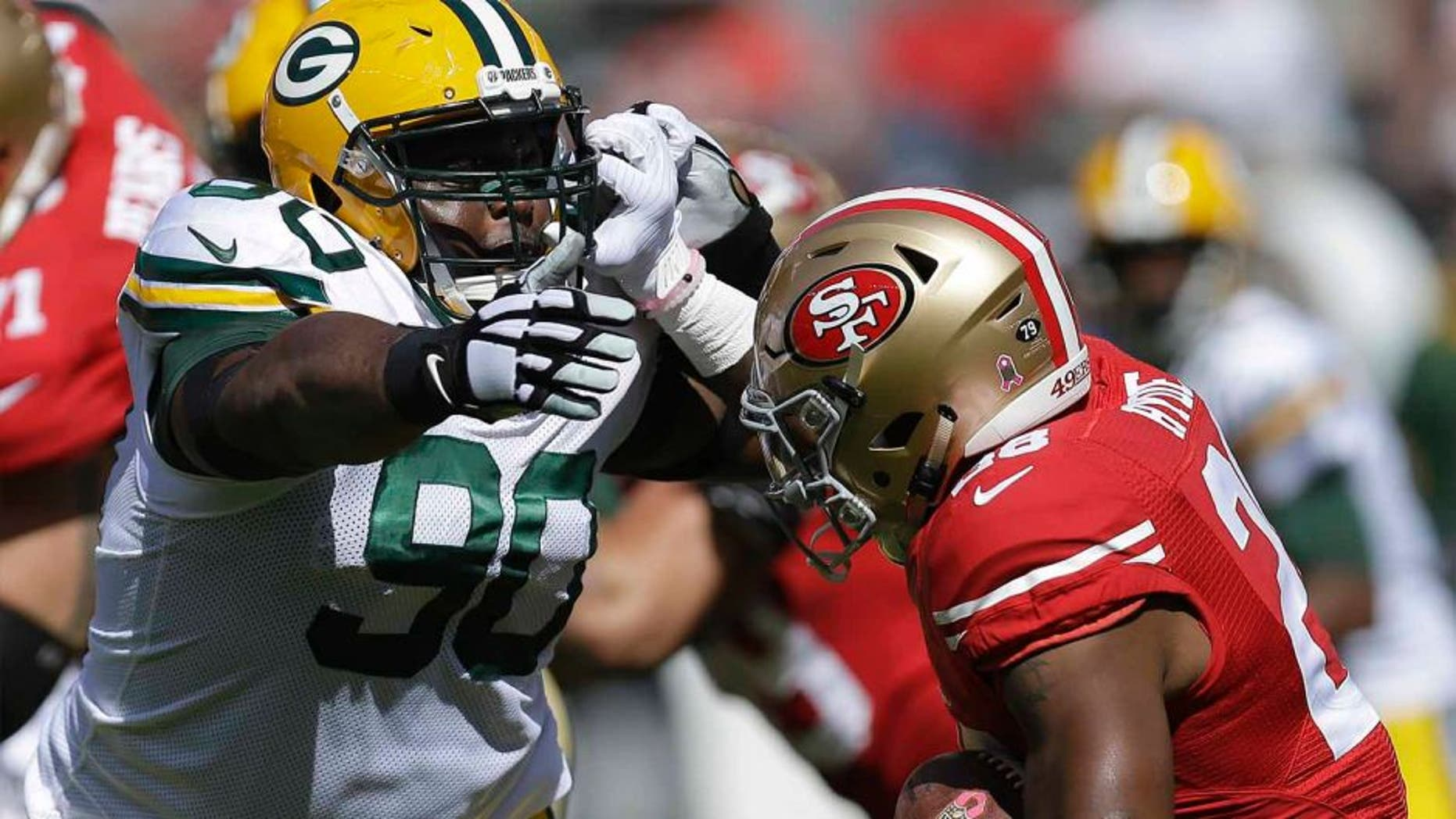 San Francisco 49ers running back Carlos Hyde (right) runs against Green Bay Packers nose tackle B.J. Raji during the first half in Santa Clara, Calif., on Sunday, Oct. 4, 2015.