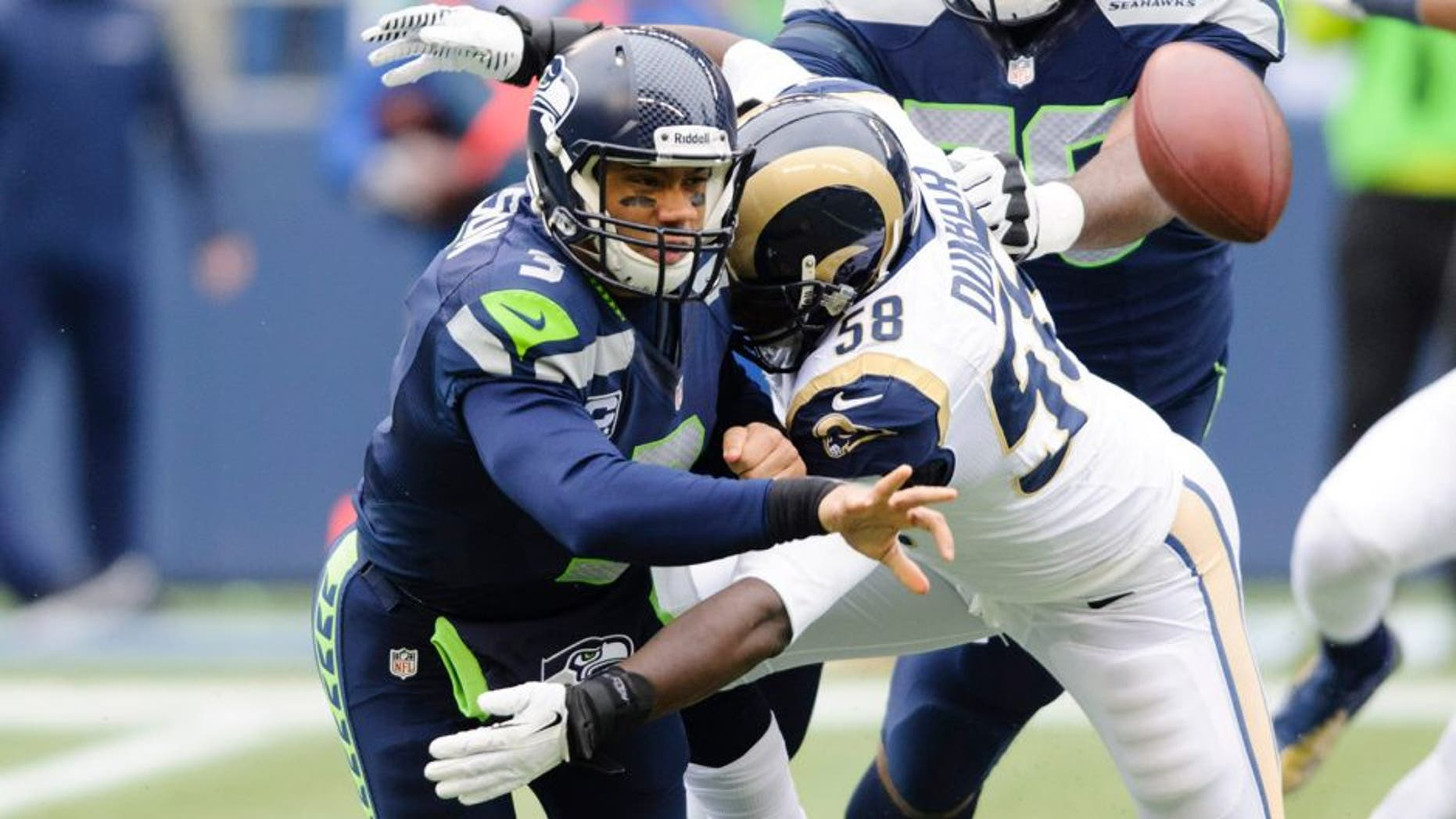 Dec 29, 2013; Seattle, WA, USA; Seattle Seahawks quarterback Russell Wilson (3) throws the ball as St. Louis Rams outside linebacker Jo-Lonn Dunbar (58) tackles during the first half at CenturyLink Field. Mandatory Credit: Steven Bisig-USA TODAY Sports