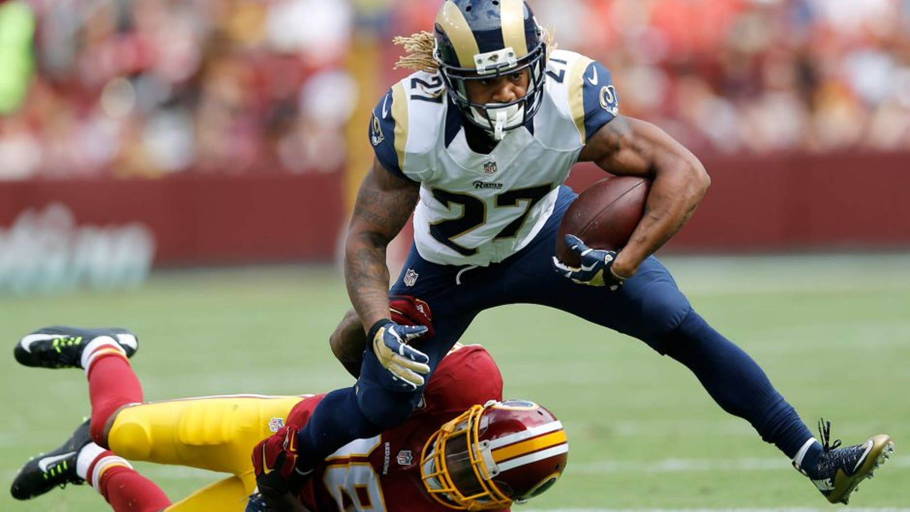 Washington Redskins free safety Dashon Goldson (38) pulls St. Louis Rams running back Tre Mason (27) to the turf during the second half of an NFL football game in Landover, Md., Sunday, Sept. 20, 2015. (AP Photo/Patrick Semansky)