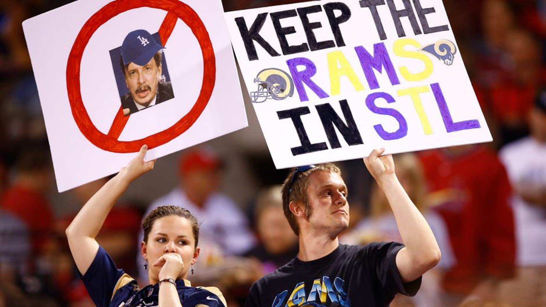 "Fans hold up signs with a picture of St. Louis Rams owner Stan Kroenke and ""Keep the Rams in STL"" during a baseball game between the St. Louis Cardinals and Los Angeles Dodgers, Friday, May 29, 2015, in St. Louis. (AP Photo/Billy Hurst)"