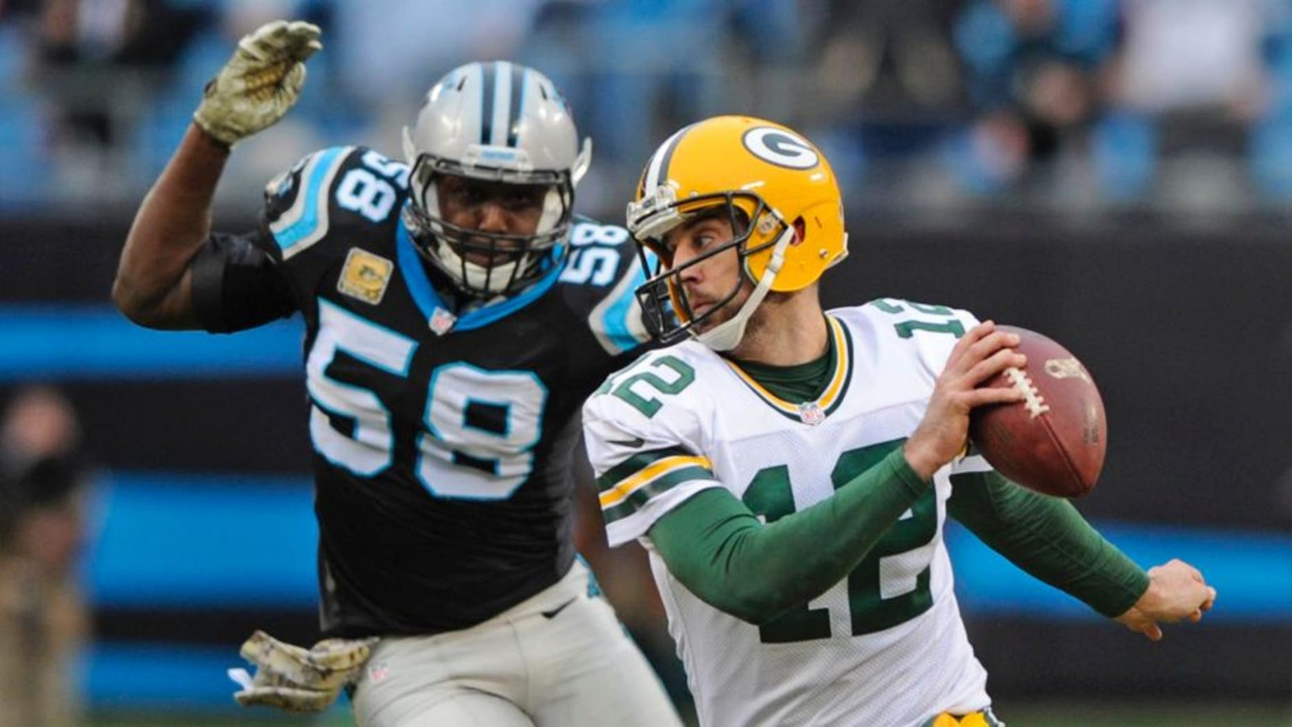 The Green Bay Packers' Aaron Rodgers scrambles as the Carolina Panthers' Thomas Davis pursues in the second half of an NFL football game in Charlotte, N.C., on Sunday, Nov. 8, 2015.