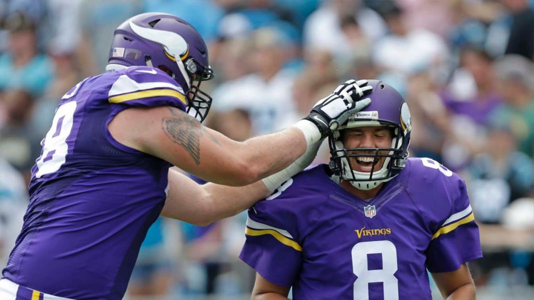 The Minnesota Vikings' Sam Bradford (right) is congratulated by Jeremiah Sirles after touchdown pass against the Carolina Panthers in the second half in Charlotte, N.C., Sunday, Sept. 25, 2016.