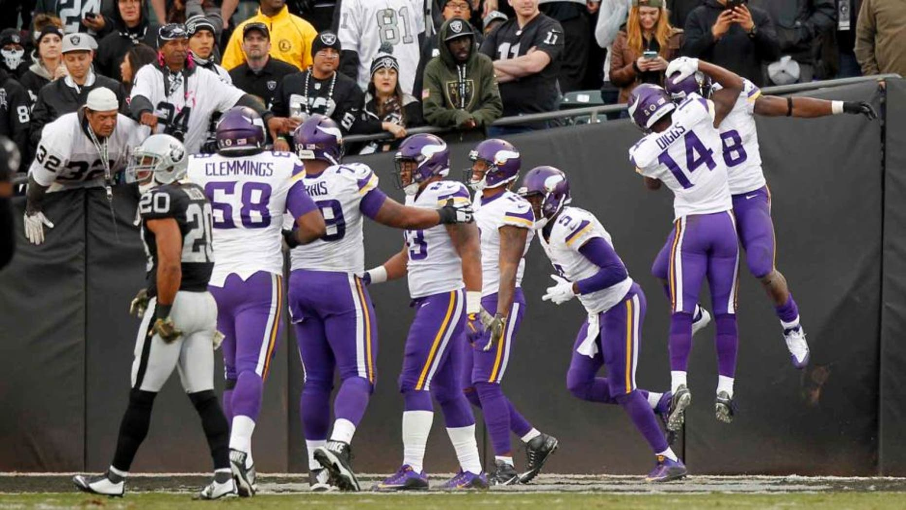 Minnesota Vikings running back Adrian Peterson (right) is congratulated by wide receiver Stefon Diggs (second from right) after rushing for a touchdown against the Oakland Raiders in the fourth quarter at O.co Coliseum in Oakland, Calif., on Sunday, Nov. 15, 2015. The Vikings won 30-14.