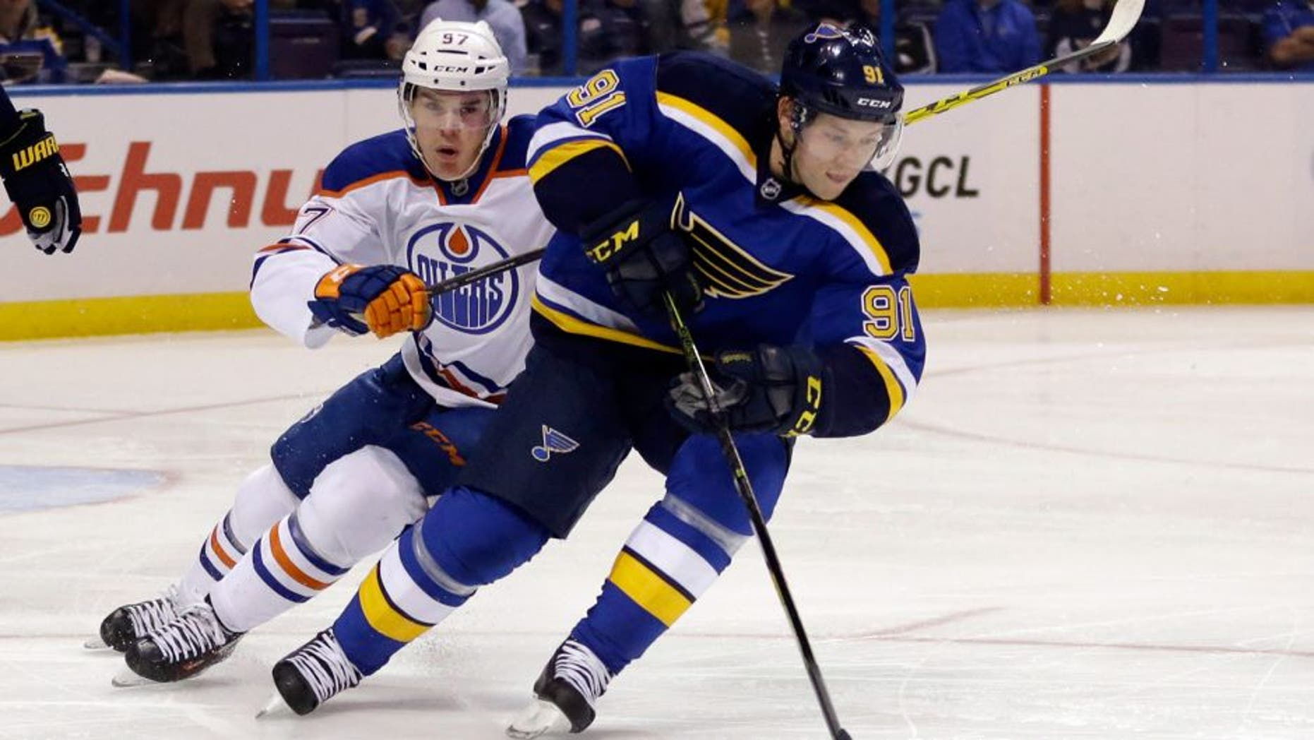 St. Louis Blues' Vladimir Tarasenko, right, of Russia, controls the puck as Edmonton Oilers' Connor McDavid, left, pursues during the first period of an NHL hockey game Thursday, Oct. 8, 2015, in St. Louis. (AP Photo/Jeff Roberson)