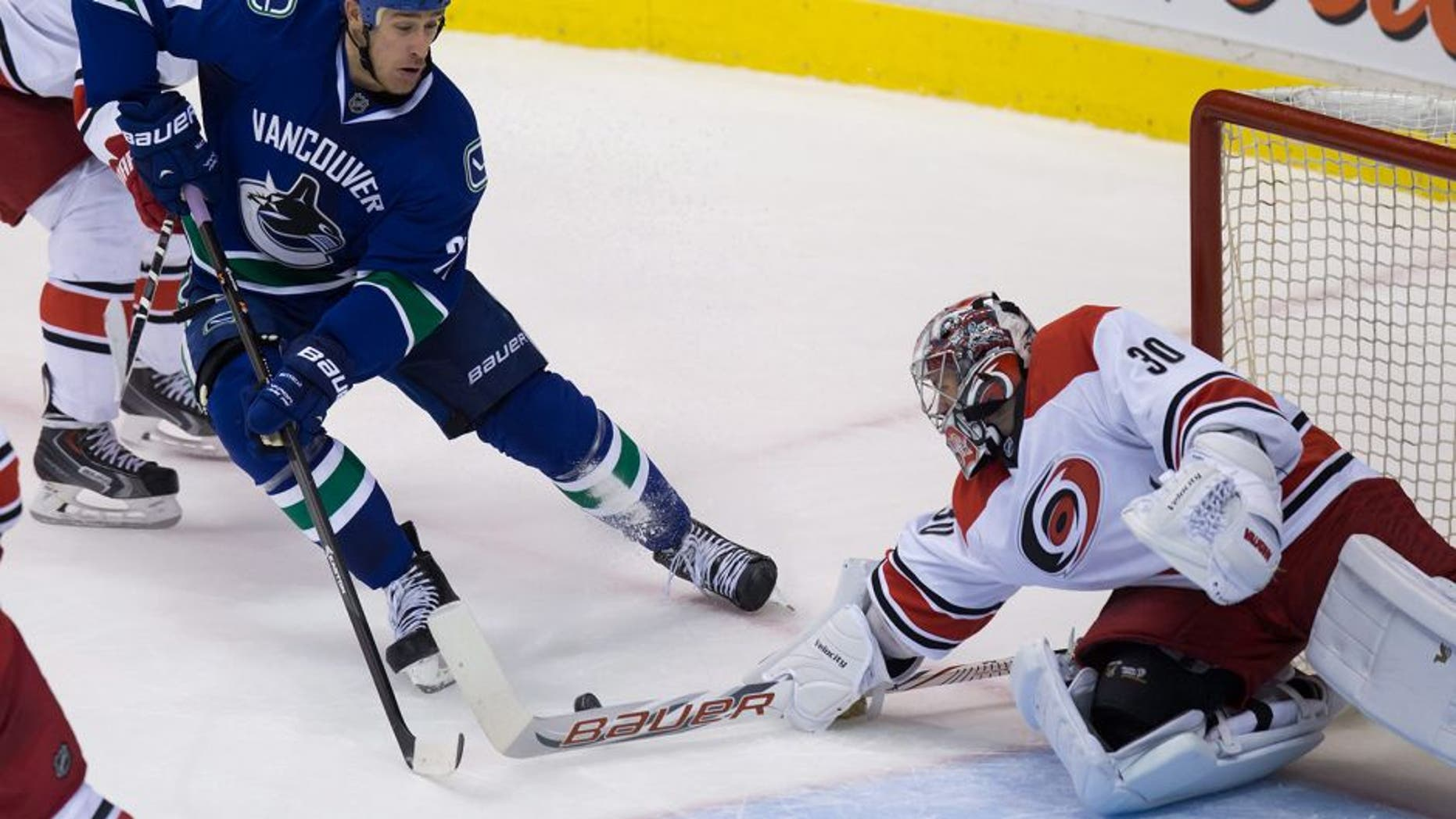 Vancouver Canucks' Shawn Matthias, left, is stopped by Carolina Hurricanes goalie Cam Ward during the second period of an NHL hockey game, Tuesday, Oct. 28, 2014 in Vancouver, British Columbia. (AP Photo/The Canadian Press, Darryl Dyck)