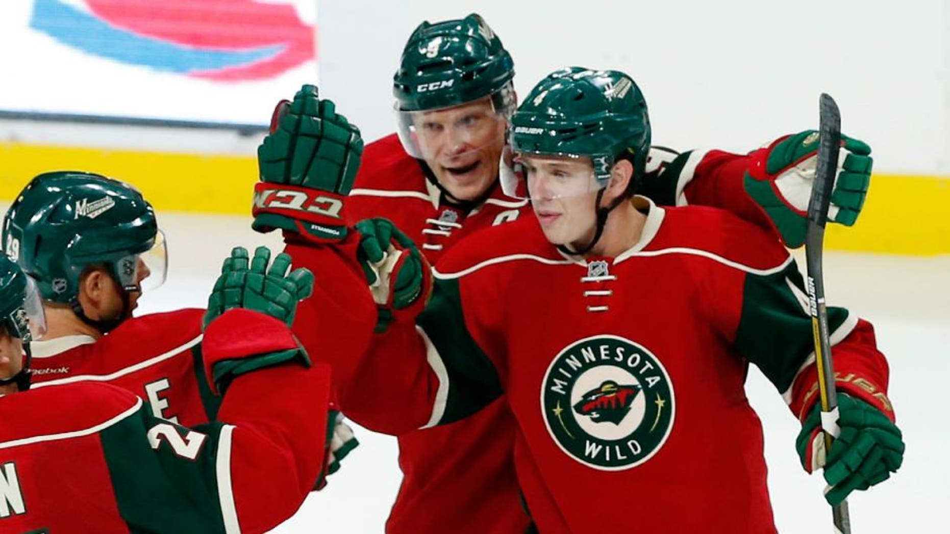 The Minnesota Wild's Mike Reilly, right, is congratulated by teammates after he scored the go-ahead goal in the third period off Winnipeg Jets goalie Michael Hutchinson.