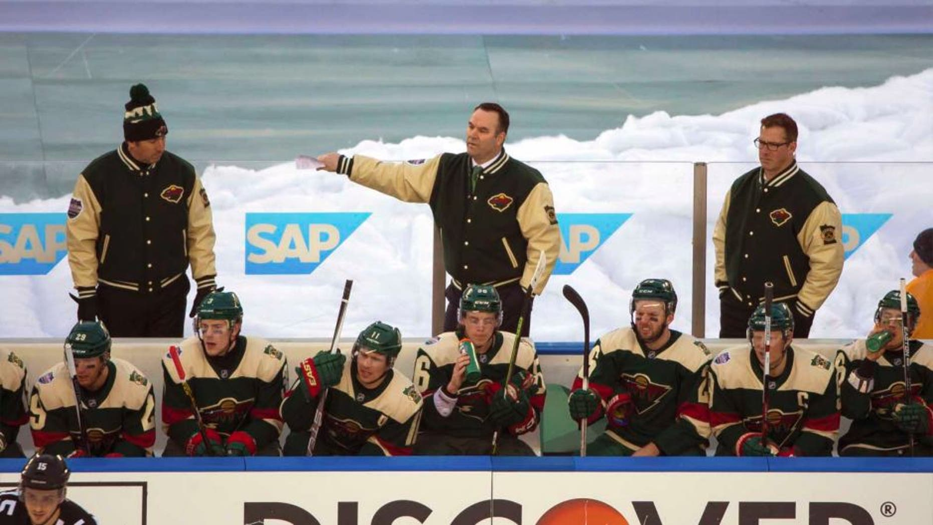 Minnesota Wild interim head coach John Torchetti stands behind the bench in the third period against the Chicago Blackhawks during a Stadium Series hockey game at TCF Bank Stadium in Minneapolis on Sunday, Feb. 21, 2016.