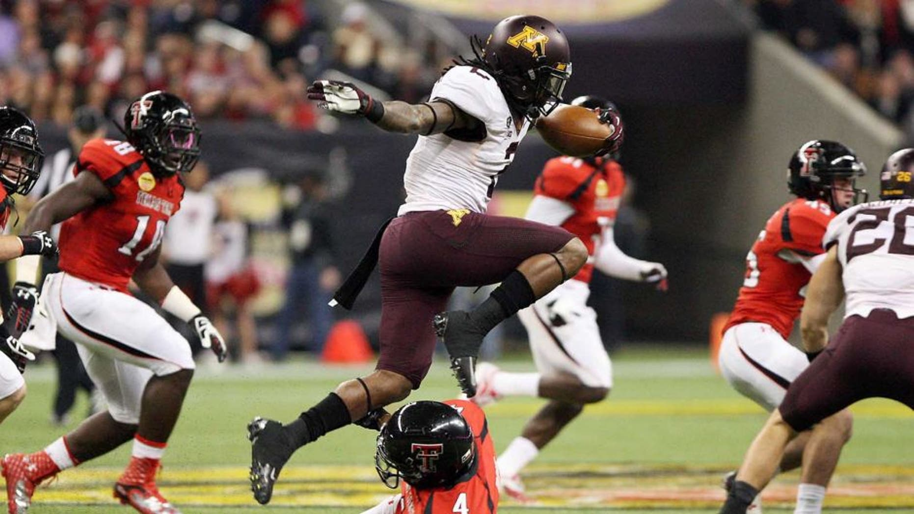 Dec 28, 2012; Houston, TX, USA; Minnesota Golden Gophers defensive back Troy Stoudermire (2) leaps over a defender on a kickoff return against the Texas Tech Red Raiders during the first quarter of the Car Care Bowl at Reliant Stadium. Mandatory Credit: Troy Taormina-USA TODAY Sports