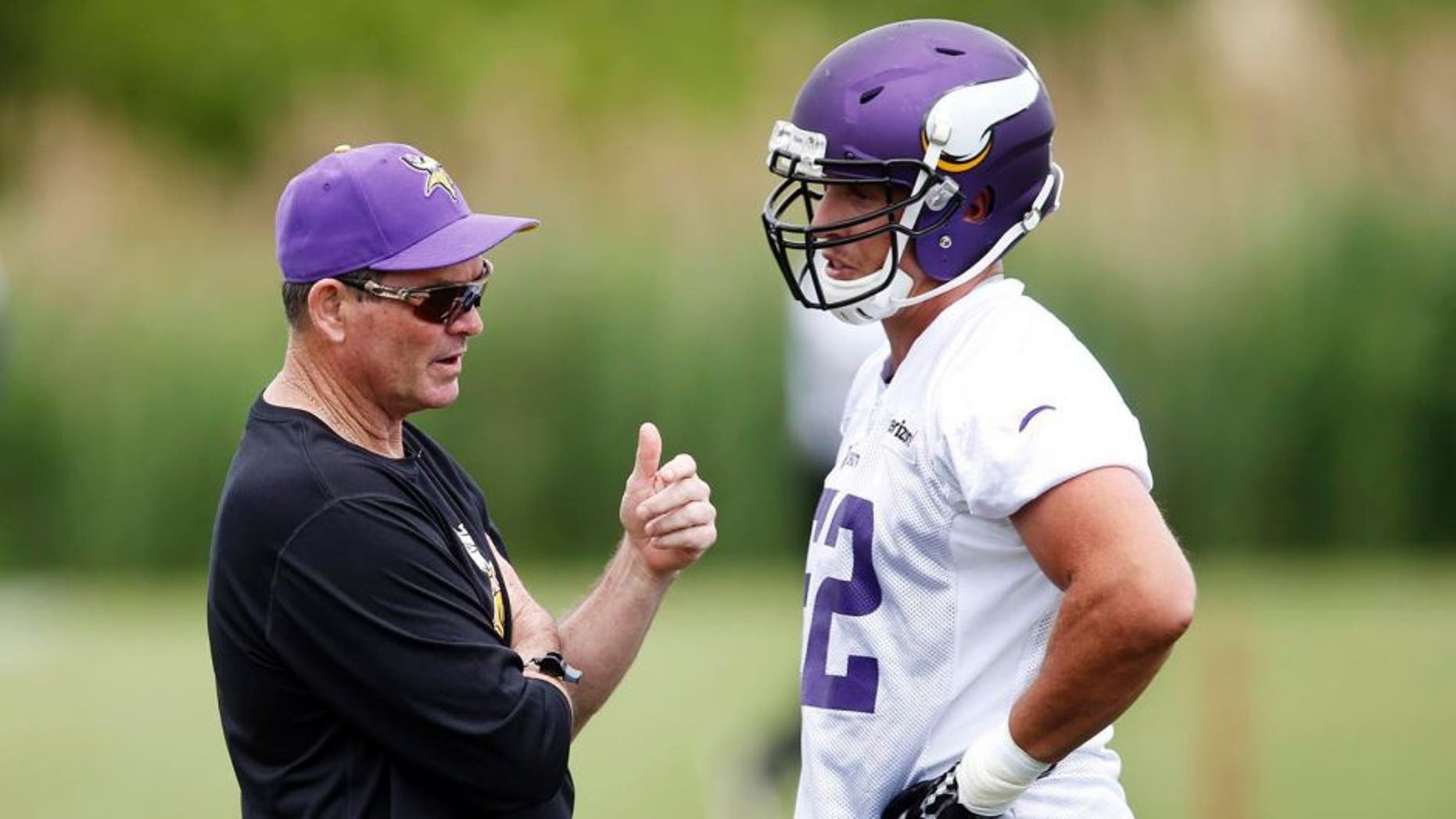Minnesota Vikings head coach Mike Zimmer visits with linebacker Chad Greenway.