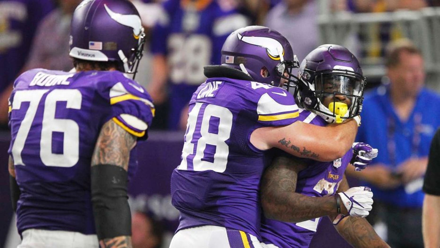 Minnesota Vikings running back Jerick McKinnon, right, celebrates with teammates Zach Line, center, and Alex Boone, left, after scoring on a 4-yard touchdown run during the second half of an NFL football game against the New York Giants, Monday, Oct. 3, 2016, in Minneapolis. (AP Photo/Andy Clayton-King)
