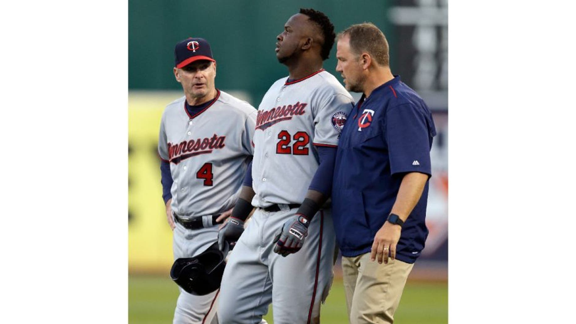 Minnesota Twins manager Paul Molitor, left, and a trainer walk Miguel Sano off the field after an injury sustained in the third inning of a baseball game against the Oakland Athletics.