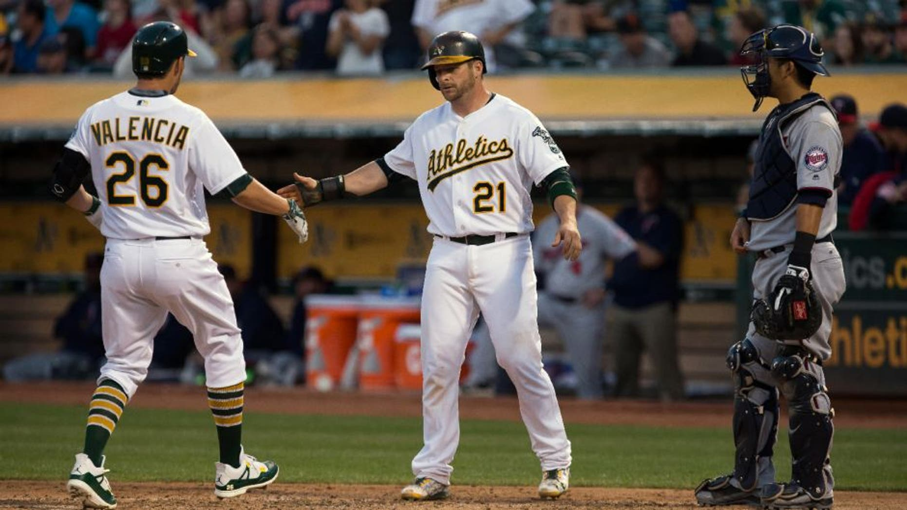 Oakland Athletics third baseman Danny Valencia is greeted by catcher Stephen Vogt after Valencia's two run home run to drive in Vogt as Minnesota Twins catcher Kurt Suzuki looks on.