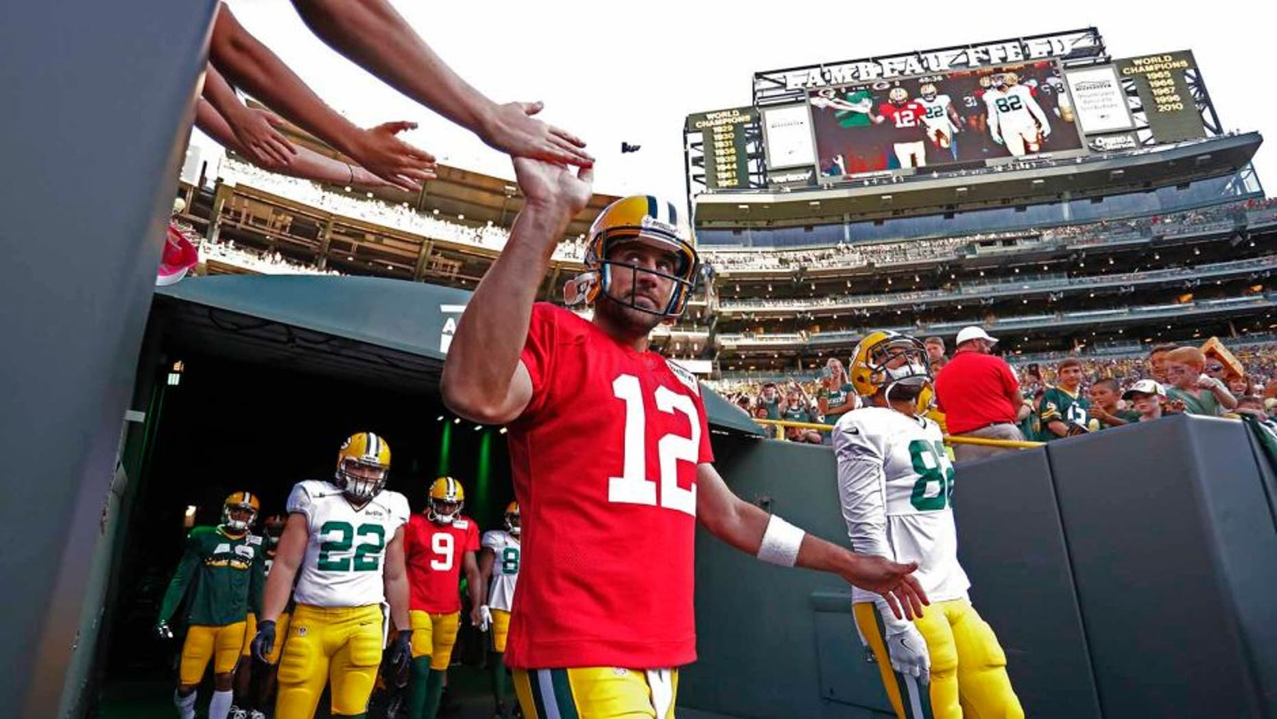 Green Bay Packers quarterback Aaron Rodgers shares a high five with a fan as he enters Lambeau Field during NFL football training camp, Sunday, July 31, 2016, in Green Bay, Wis. (AP Photo/Matt Ludtke)