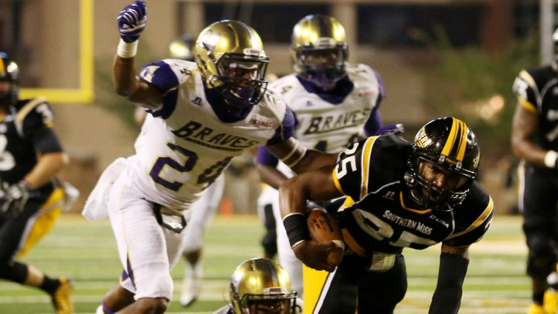 Southern Miss Golden Eagles running back Ito Smith runs with the ball as Alcorn State Braves defensive backs Warren Gatewood and Devon Francois close in.