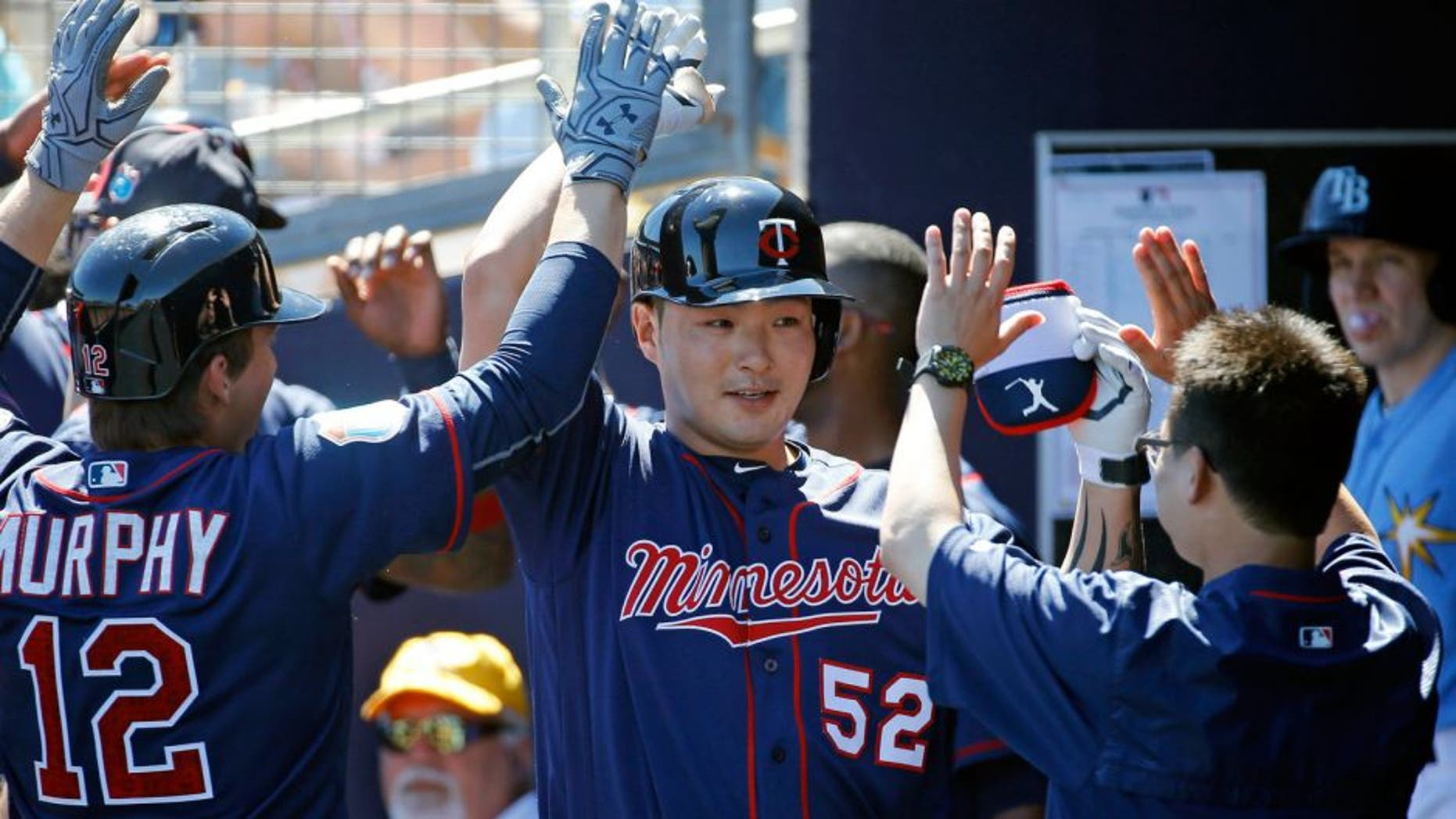 FILE - In this March 6, 2016, file photo, Minnesota Twins' Byung Ho Park, center, of South Korea, high-fives teammates in the dugout after hitting a grand slam in the first inning of a spring training baseball game against the Tampa Bay Rays in Port Charlotte, Fla. The Korean slugger is excited about making the transition from his native homeland to the major leagues this season and aims to make noise with his bat while quietly going about his business off the field and getting acclimated to life more than 7,500 miles from Seoul. (AP Photo/Patrick Semansky, FILE)