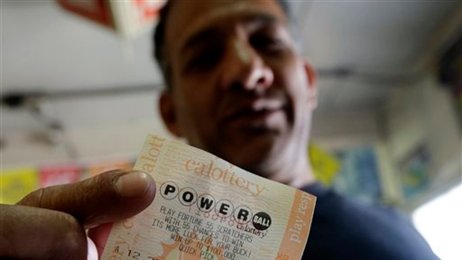 Joe Fajardo poses holding his Powerball lottery ticket after buying it at a store Saturday, May 18, 2013, in the Barrio Logan neighborhood of San Diego. With the majority of possible combinations of Powerball numbers in play, someone is almost sure to win the lottery game's highest jackpot on Saturday night, a windfall of hundreds of millions of dollars — and that's after taxes. (AP Photo/Gregory Bull)