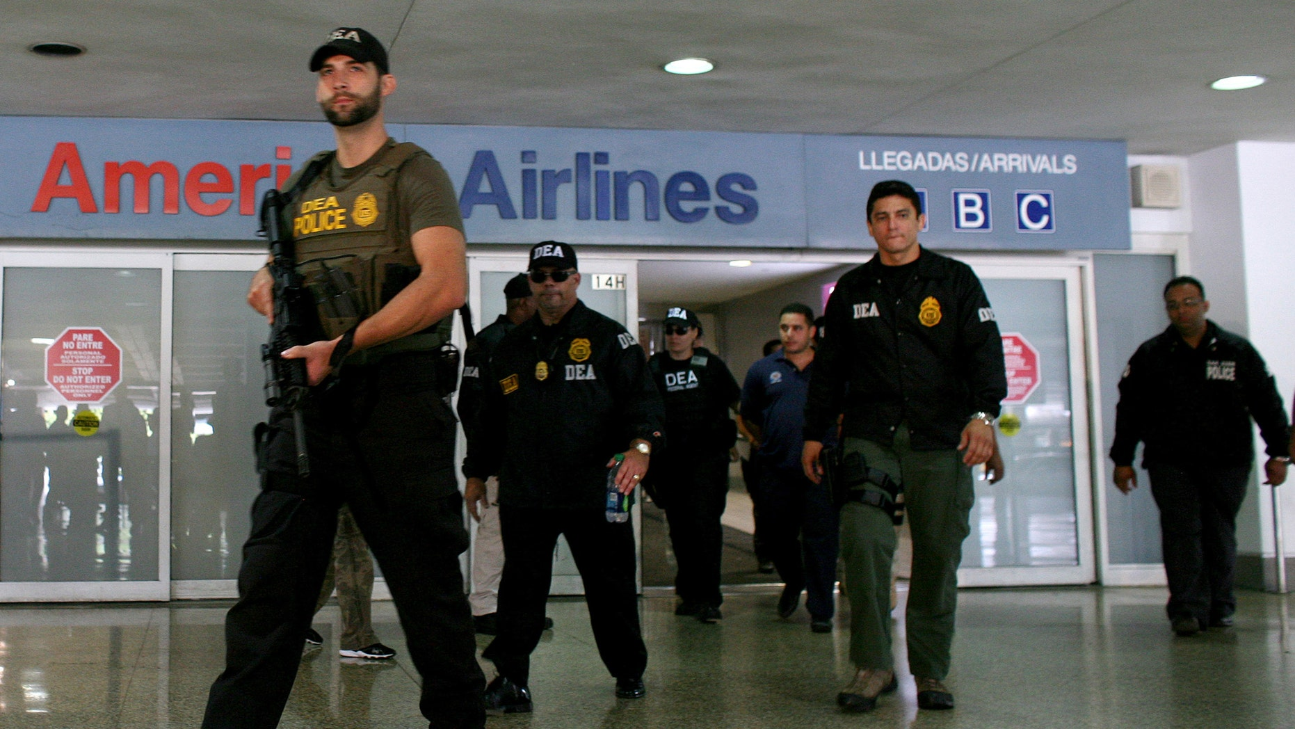 FILE - In this June 6, 2012 file photo, federal agents with the Drug Enforcement Administration escort a handcuffed drug smuggling suspect, at the airport in San Juan, Puerto Rico. U.S. federal agents will start targeting high-level drug traffickers in Puerto Rico after gathering intelligence during a three-month blitz on criminal activity in the U.S. territory, the Department of Homeland Security said Thursday, Sept. 26, 2013 (AP Photo/Ricardo Arduengo)