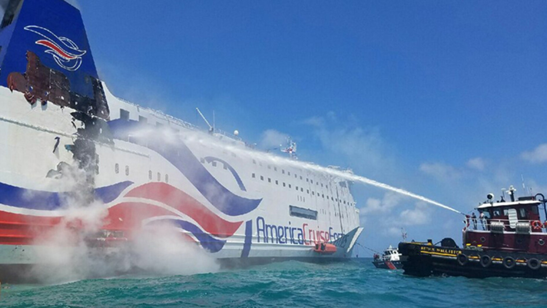 In this photo provided by the U.S. Coast Guard, a local San Juan, Puerto Rico-based tug crew uses a fire hose to cool the hull of the Caribbean Fantasy cruise ship that caught fire, a mile from San Juan Harbor, Puerto Rico, Wednesday, Aug. 17, 2016. More than 500 passengers and crew were evacuated from a burning ship off Puerto Rico's north coast and many required medical care, though there were no reported fatalities or life-threatening injuries. (Petty Officer 2nd Class Jonathan Lally/US Coast Guard via AP)