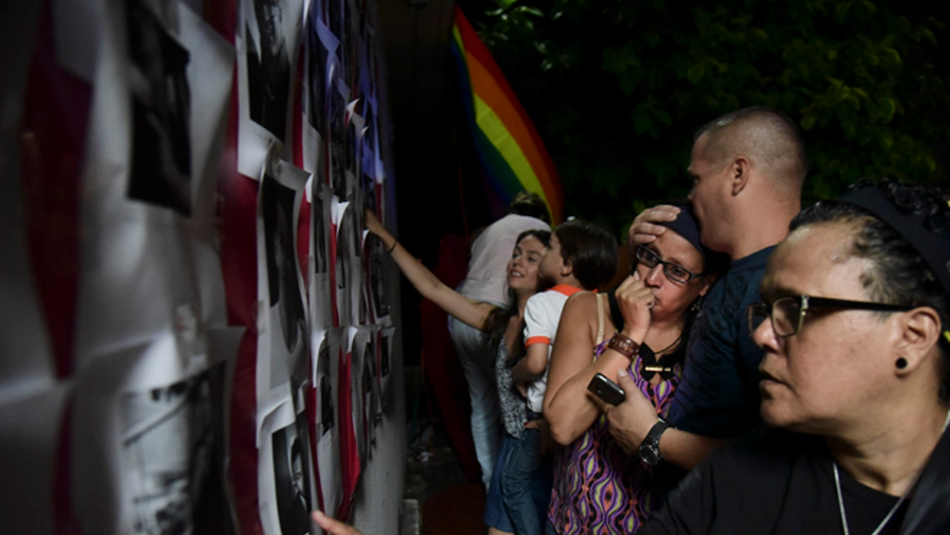 Residents look at photos of the victims during a vigil to honor the memory of the Puerto Ricans that died in the mass shooting at a nightclub in Orlando, Fla., at the Hato Rey LGBTT Community Center in San Juan, Puerto Rico, Tuesday, June 14, 2016. Dozens of people died at the 'Pulse' gay nightclub in Orlando, making it the deadliest mass shooting in modern U.S. history. (AP Photo/Carlos Giusti)