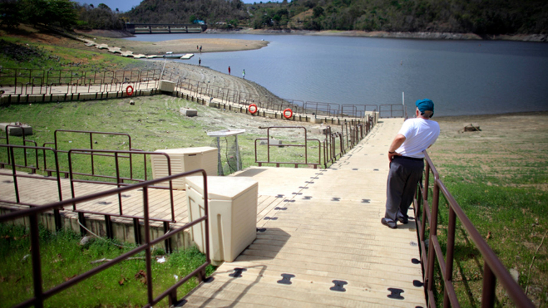 A man stands on a floating dock, laying on the unusually dry banks of the La Plata reservoir in Toa Alta, Puerto Rico, Wednesday, May 13, 2015. Puerto Rico imposed strict water-rationing measures Wednesday and Gov. Alejandro Garcia Padilla recently declared a state of emergency given the increasingly dry conditions. (AP Photo/Ricardo Arduengo)