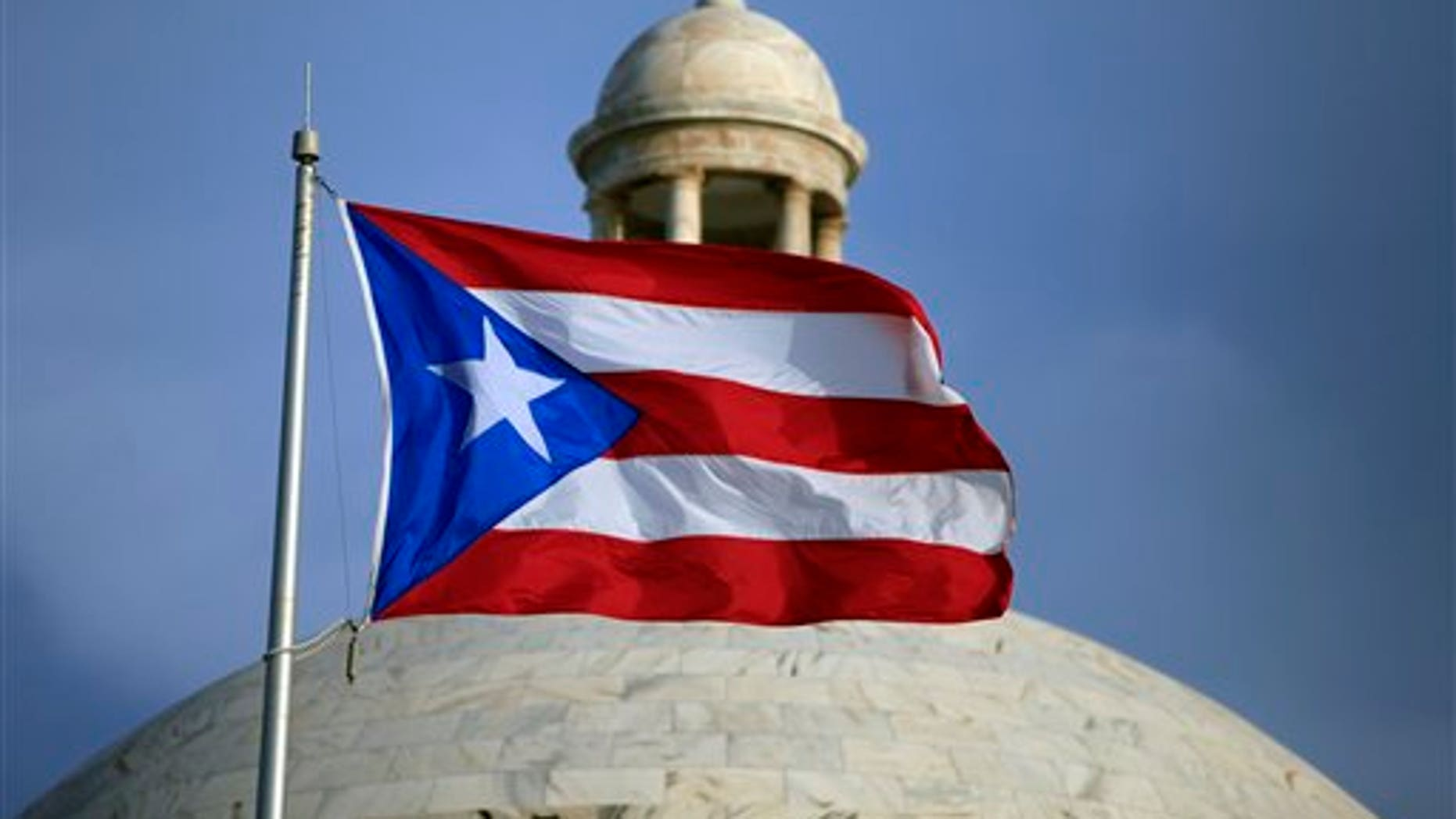 FILE - In this Wednesday, July 29, file 2015 photo, the Puerto Rican flag flies in front of Puerto Ricos Capitol as in San Juan, Puerto Rico. On Monday, April 11, 2016, Puerto Rico released a new proposal to restructure part of its $70 billion debt to buy time to implement a fiscal growth plan as multimillion-dollar payments loom for a U.S. territory facing dwindling cash reserves. (AP Photo/Ricardo Arduengo, File)