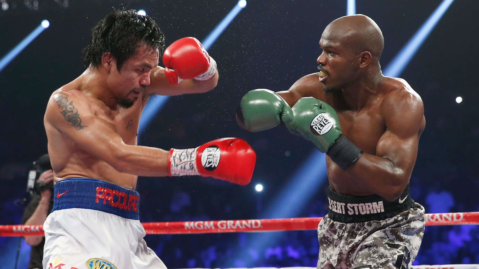 Manny Pacquiao, left, of the Philippines shields himself as Timothy Bradley throws a punch during the WBO welterweight title boxing fight Saturday, April 12, 2014, in Las Vegas. (AP Photo/Eric Jamison)