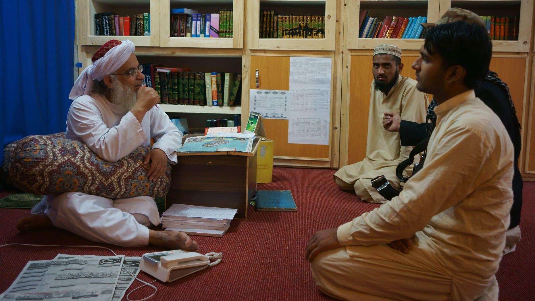 April 18, 2014 - Maulana Abdul Aziz, left, head cleric of a Pakistani seminary, in a library named after slain al Qaeda leader Usama bin Laden in Islamabad, Pakistan.