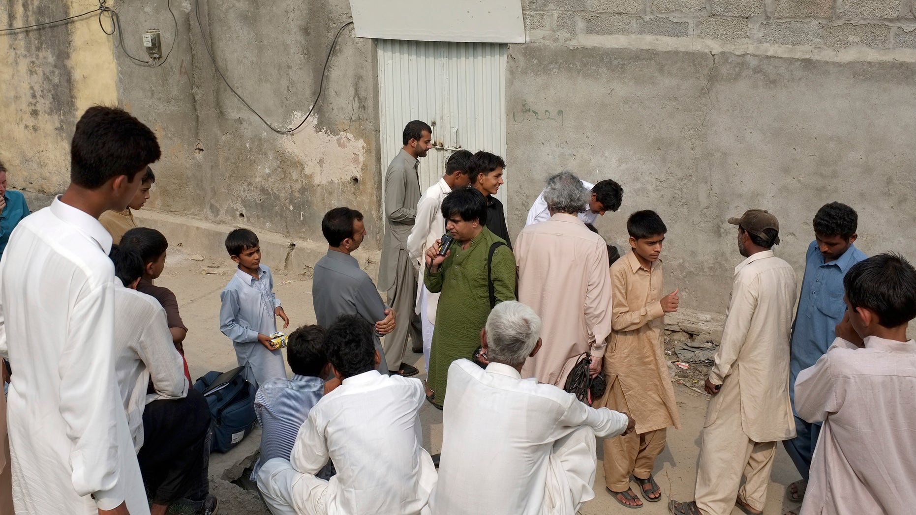 Aug. 20- People gathered outside the locked house of a Christian girl in suburbs of Islamabad, Pakistan. Pakistani authorities arrested a Christian girl and are investigating whether she violated the country's strict blasphemy laws.