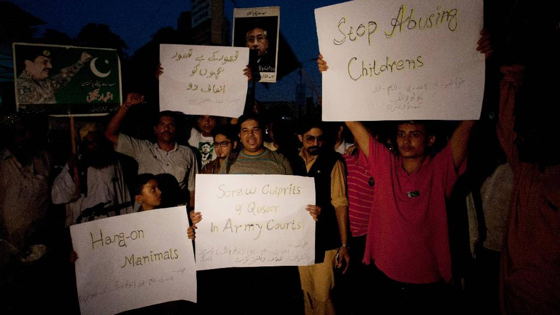 """Activists from Pakistan's civil society hold placards to condemn a child abuse scandal, while holding a rally in Karachi, Pakistan, Tuesday, Aug. 11, 2015. In the Pakistani town of Hussain Khan Wala, near the border with India, families kept quiet for years about the blackmail gang that locals believe filmed some 270 children being sexually abused, fearful the videos could appear online or sold in markets for as little as 50 cents. The placard at upper left reads in Urdu, """"Give justice to innocent children."""" (AP Photo/Shakil Adil)"""