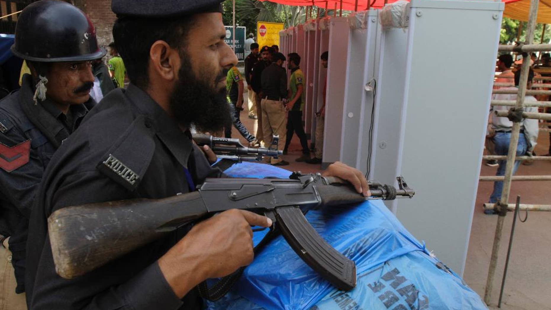 Pakistani police officers stand alert at an entrance of the Gaddafi stadium during the  second one-day international match between Pakistan and Zimbabwe Friday, May 29, 2015. Zimbabwe is the first test playing nation to visit Pakistan in more than six years since gunmen attacked a bus of the Sri Lanka team in Lahore in 2009. (AP Photo/K.M. Chaudary)