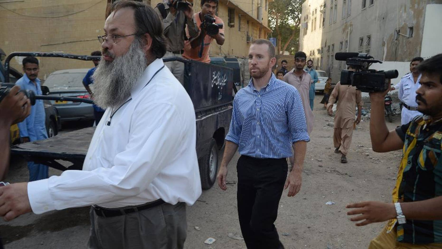 An American national, center, reportedly working for the FBI, leaves a police station in Karachi, Pakistan, Thursday, May 8, 2014. Pakistan released an FBI agent on bail Thursday after three days in custody, officials said, a move that is likely to prevent the situation from escalating into a diplomatic spat. The American man was detained after airport authorities found him carrying ammunition and three knives Monday as he was about to board a flight for the Pakistani capital, Islamabad.(AP Photo/Mohammad Khalil)