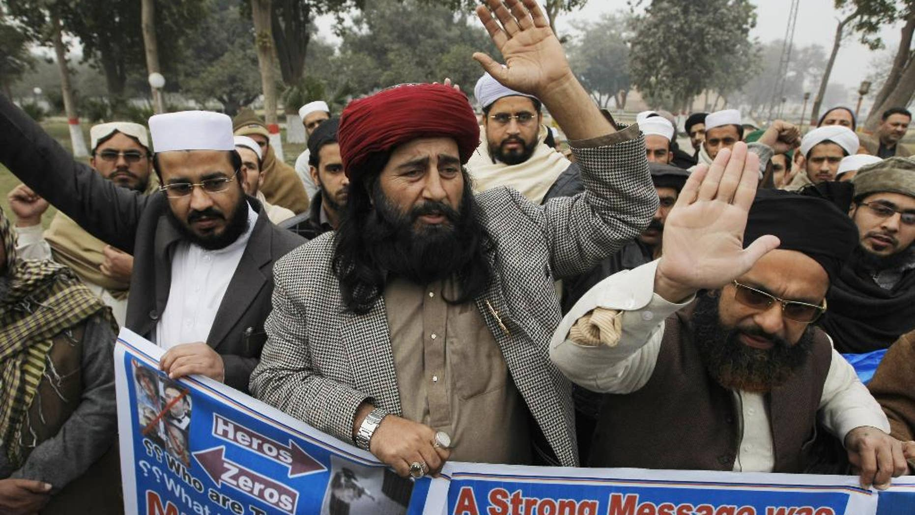 People rally to pay tribute to attackers of the satirical magazine Charlie Hedbo in Paris, Tuesday, Jan. 13, 2015 in Peshawar, Pakistan. The hardline Pakistani cleric in the country's northwest has led a prayer service in honor of the two brothers who attacked the satirical magazine Charlie Hedbo in Paris. (AP Photo/Mohammad Sajjad)