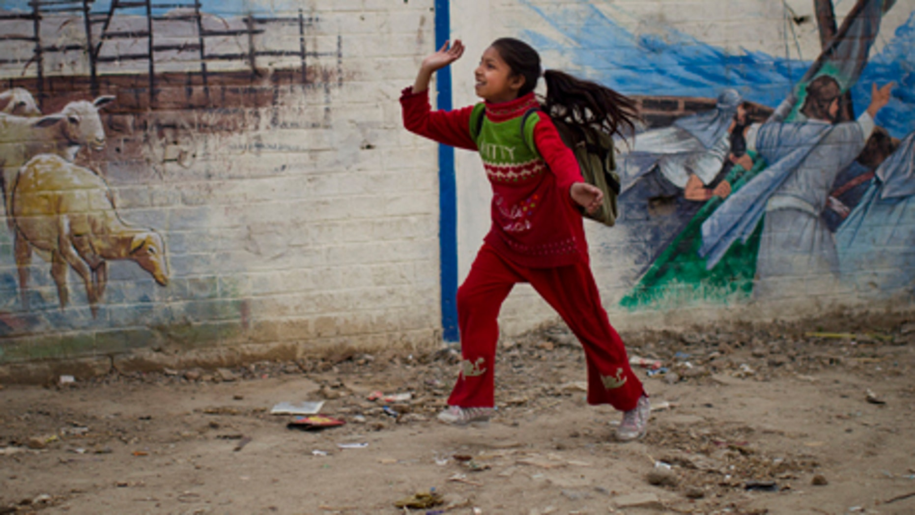 March 11, 2012: A Pakistani Christian girl plays with a balloon next to a wall with biblical paintings at the Christian colony in the center of Islamabad, Pakistan. Roughly five percent of Pakistan's 180 million people belong to minority religions, which include Hindu, Christian, Shiite Muslims and Ahmedis, according to the CIA World Factbook.