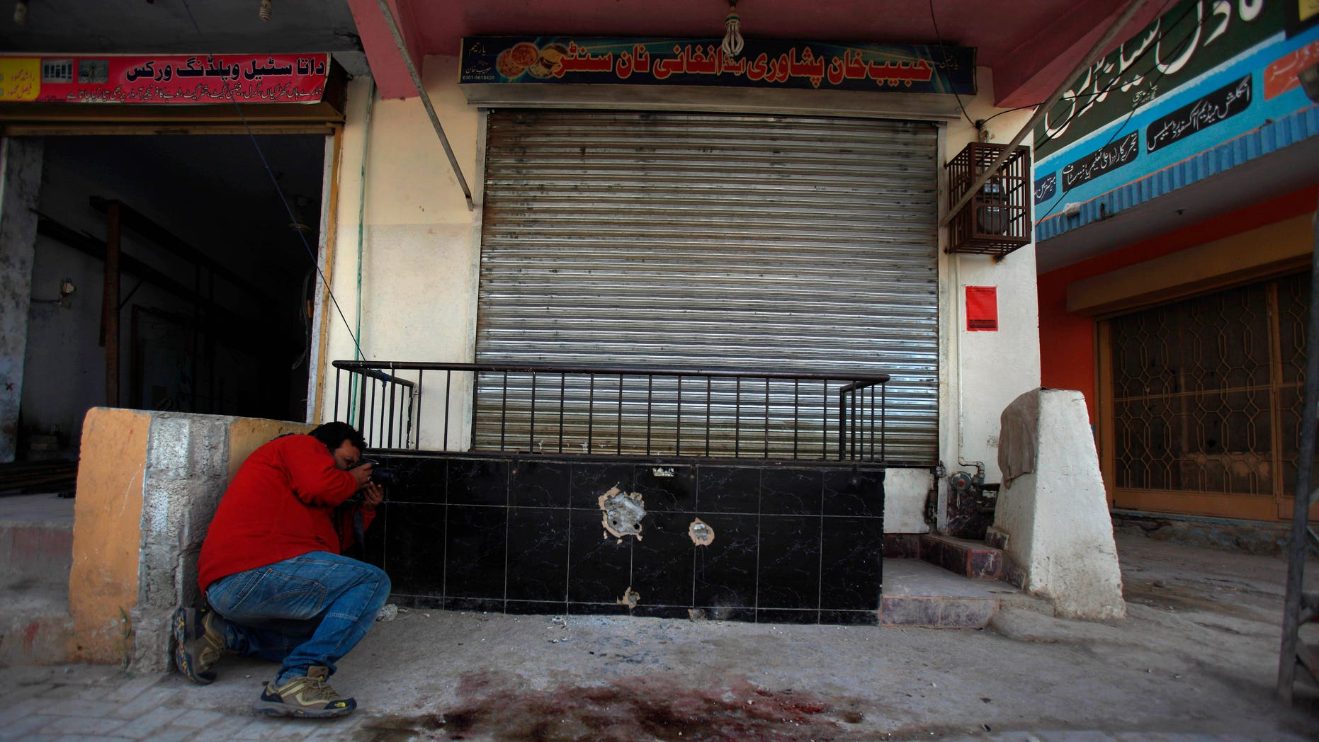 Nov. 11, 2013 - A photographer takes picture of the spot where Nasiruddin Haqqani, a senior leader of the feared militant Haqqani network, was assassinated at an Afghan bakery in the Bhara Kahu area on the outskirts of Islamabad, Pakistan.