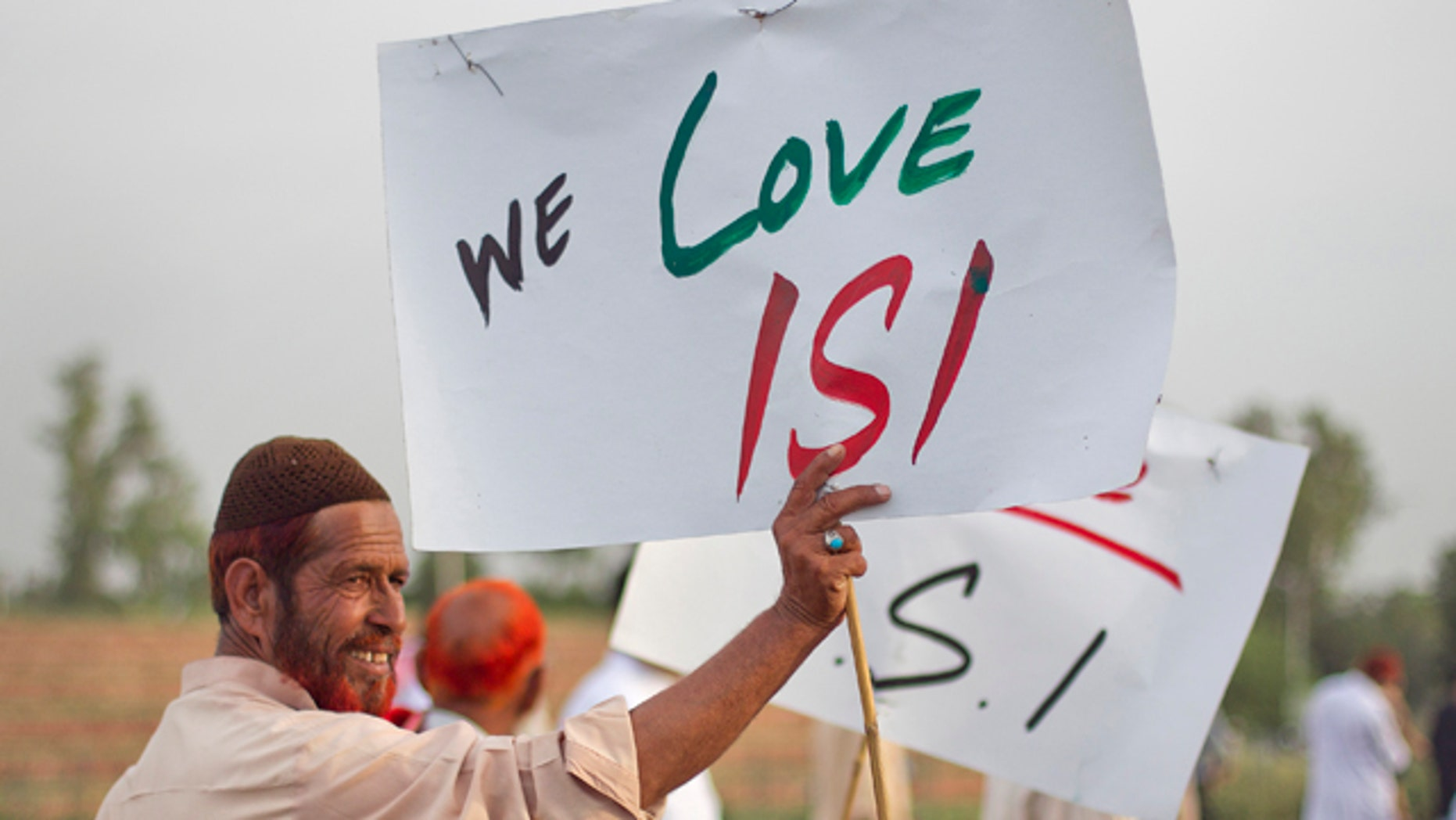 May 11, 2011: An activist associated with a social group from a citizen forum holds a placard as protesters rally in favor of Pakistan's army and Inter-Services Intelligence (ISI) in Islamabad.
